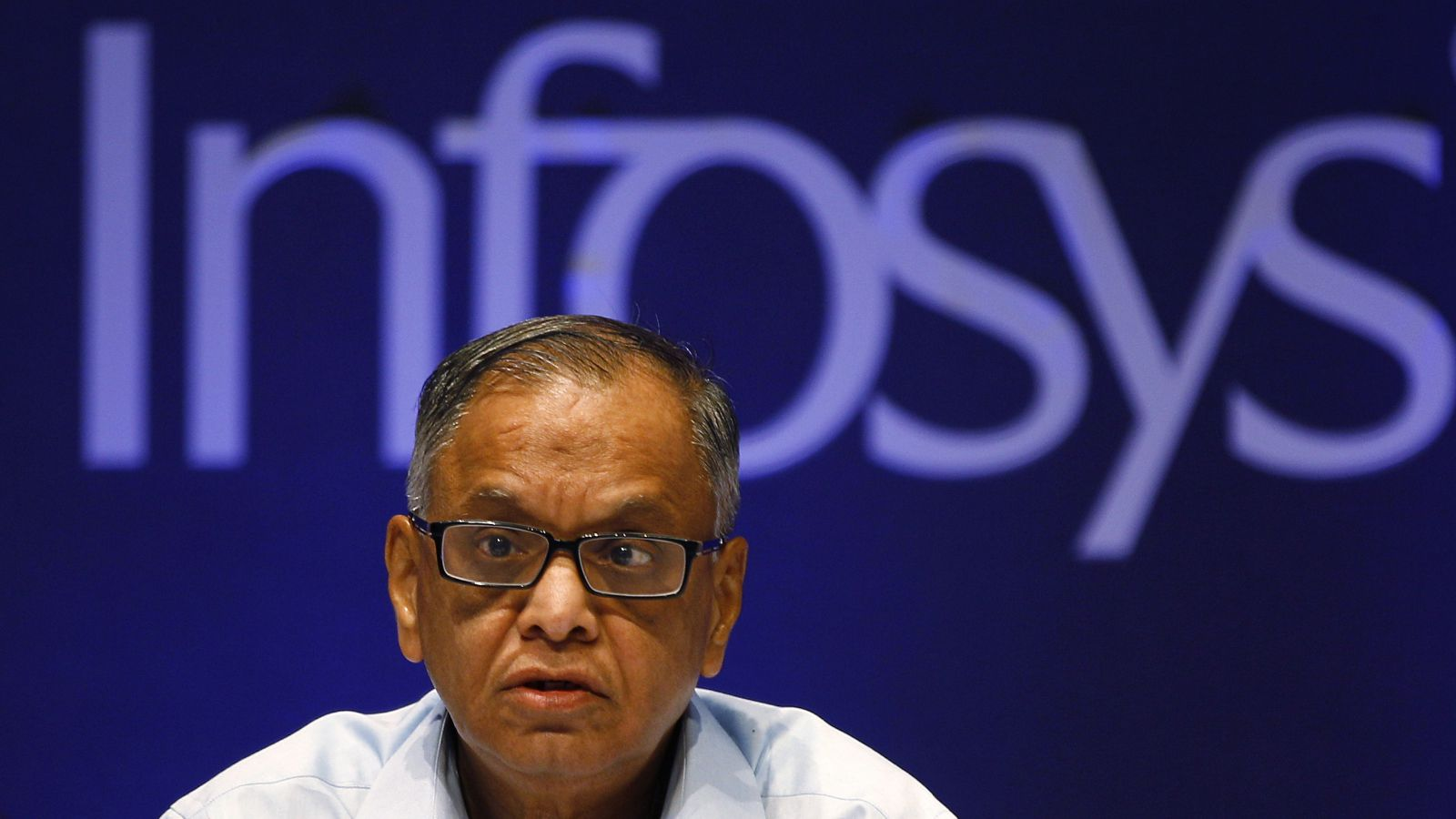 In this June 15, 2013 file photo, Infosys Executive Chairman N. R. Narayana Murthy reacts to a shareholders comment during the company's 32th Annual General Meeting in Bangalore, India. In 2013 Infosys was accused of bringing thousands of foreign workers to the United States using incorrect visas, but denied any allegations as part of the settlement reached with a $34 million settlement in Texas.