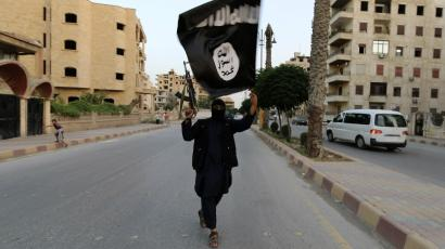 A member loyal to the Islamic State in Iraq and the Levant waves an ISIL flag in Raqqa, June 29, 2014.