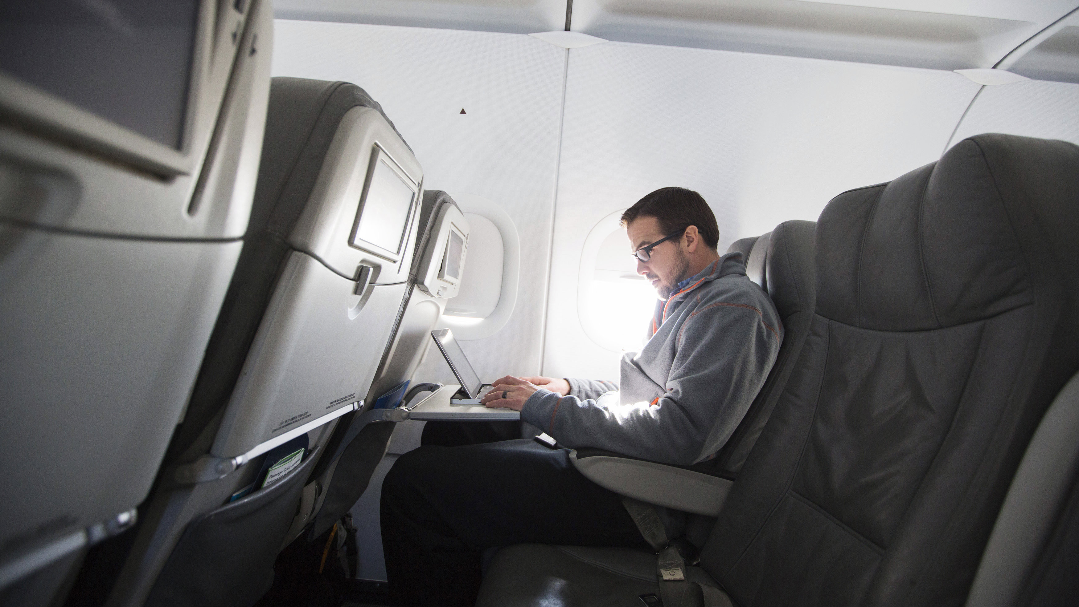 A man uses his laptop to test a new high speed inflight Internet service named Fli-Fi while on a special JetBlue media flight out of John F. Kennedy International Airport in New York December 11, 2013. Wi-Fi in the sky is taking off, promising much better connections for travelers and a bonanza for the companies that sell the systems. With satellite-based Wi-Fi, Internet speeds on jetliners are getting lightning fast. And airlines are finding that travelers expect connections in the air to rival those on the ground - and at lower cost. Picture taken December 11, 2013. To match Analysis AIRLINES-WIFI/