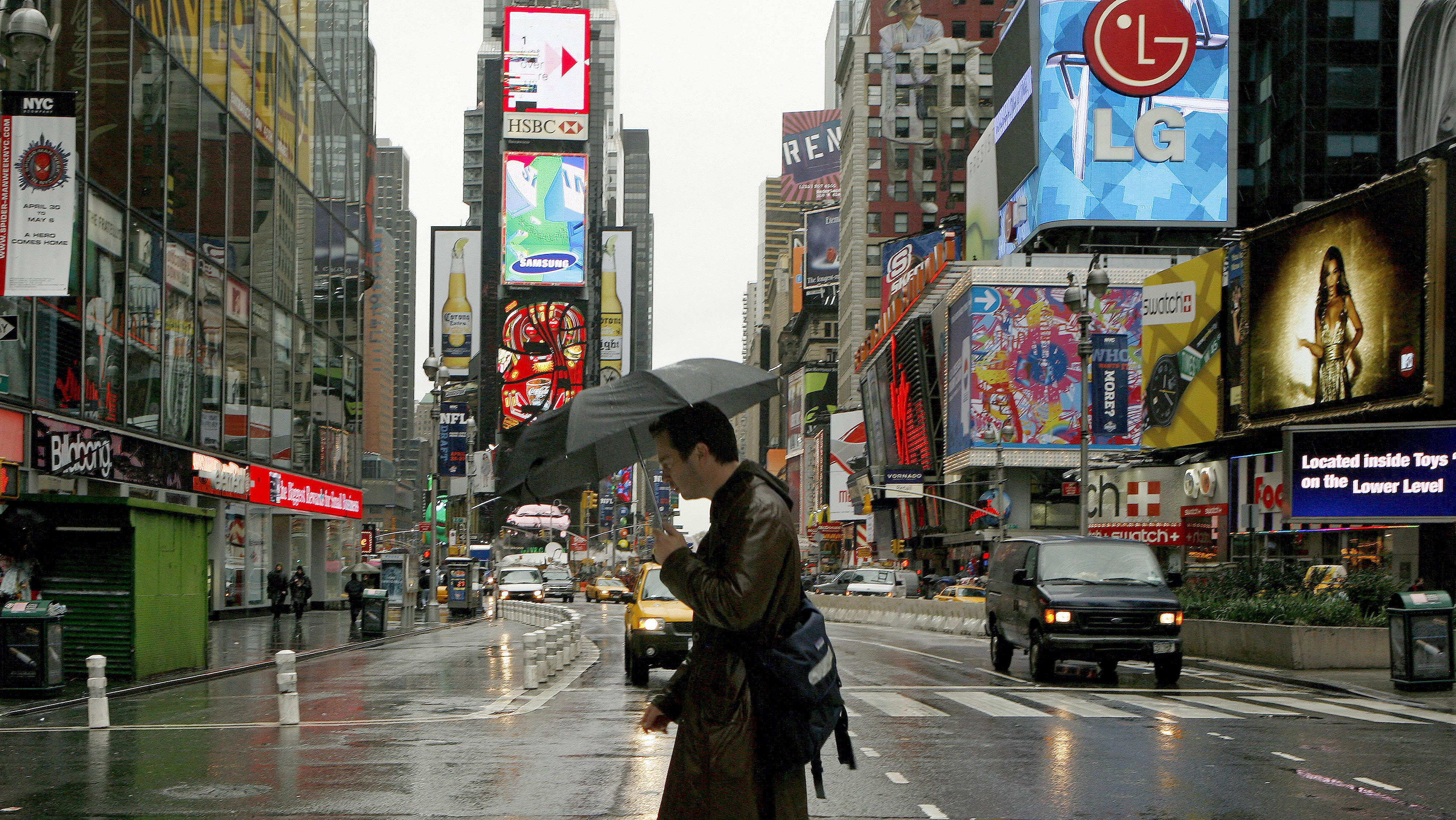 man walking through times square surrounded by advertisements