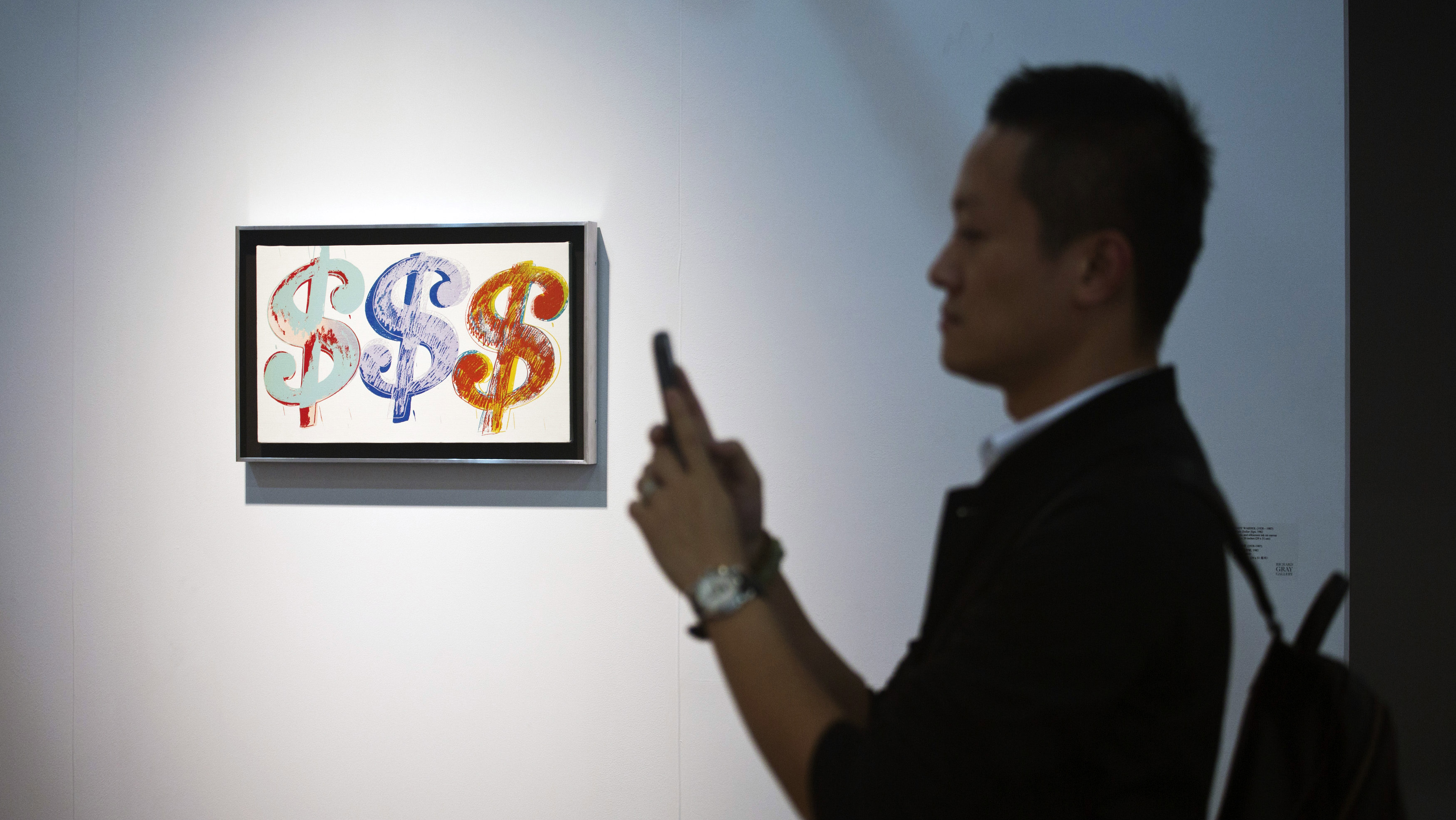 """A man takes pictures with his phone next to an artwork titled """"Triple Dollar Sign"""" by U.S. artist Andy Warhol during a preview of the first Art Basel in Hong Kong May 22, 2013. Founded by gallerists in 1970, the Art Basel is an international art show which has been held annually in Basel and Miami Beach. Its debut in Hong Kong features modern and contemporary artworks by more than 2,000 artists from Asia and around the world, and runs from May 23 to 26, according to the event's news release."""