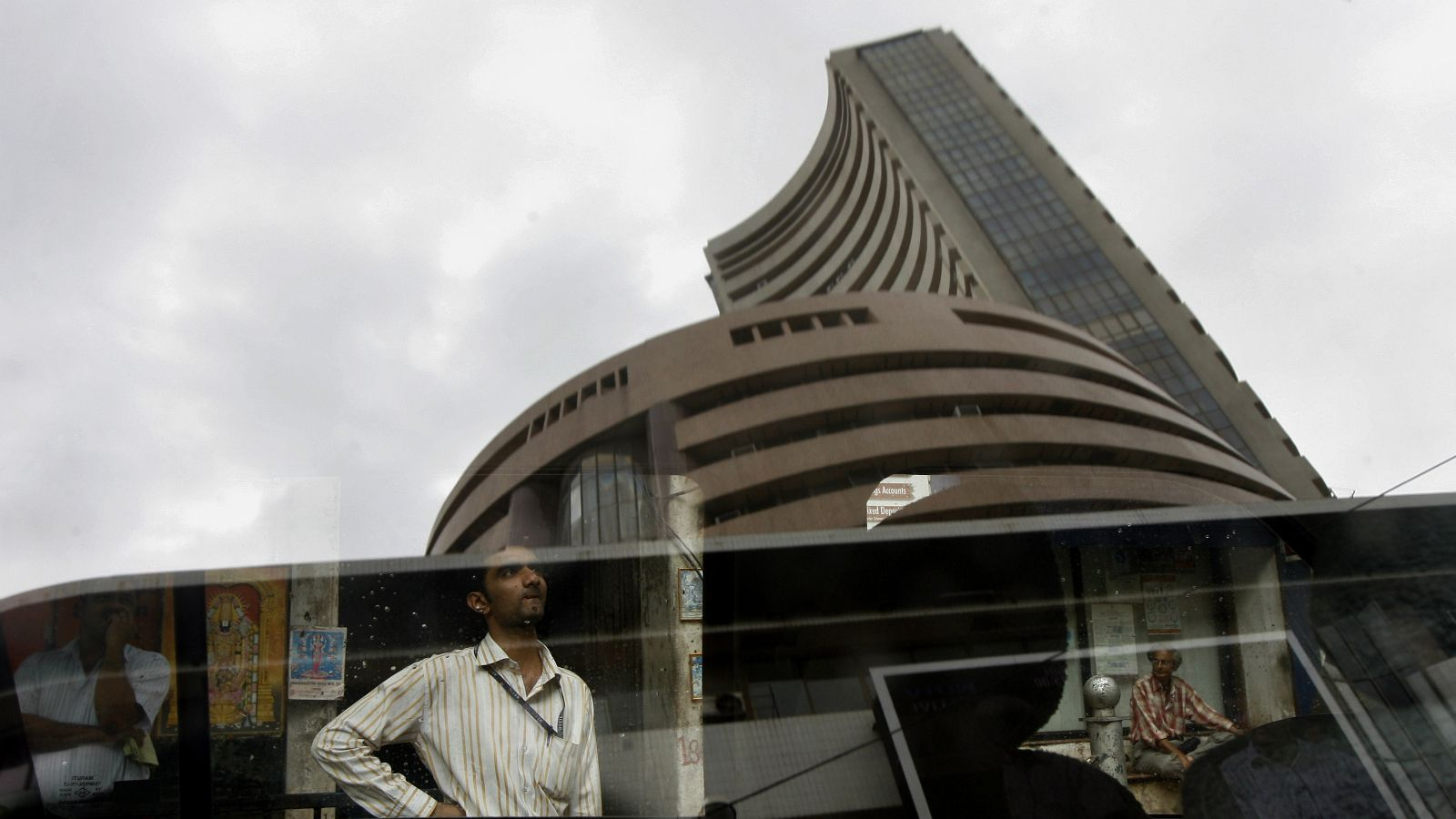 The Bombay Stock Exchange (BSE) building is reflected on a glass window as people look at a large screen displaying India's benchmark share index on the facade of the building in Mumbai July 2, 2008. Beaten down Indian shares rose 5.4 percent on Wednesday, their biggest single-day gain in more than three months, as investors picked up bargains but analysts said high oil prices and political stability were concerns. The rebound was underpinned by gains in European shares and U.S. stock index futures that pointed to a rise on Wall Street, and hectic short covering after the market had slid more than 10 percent in the previous three sessions.