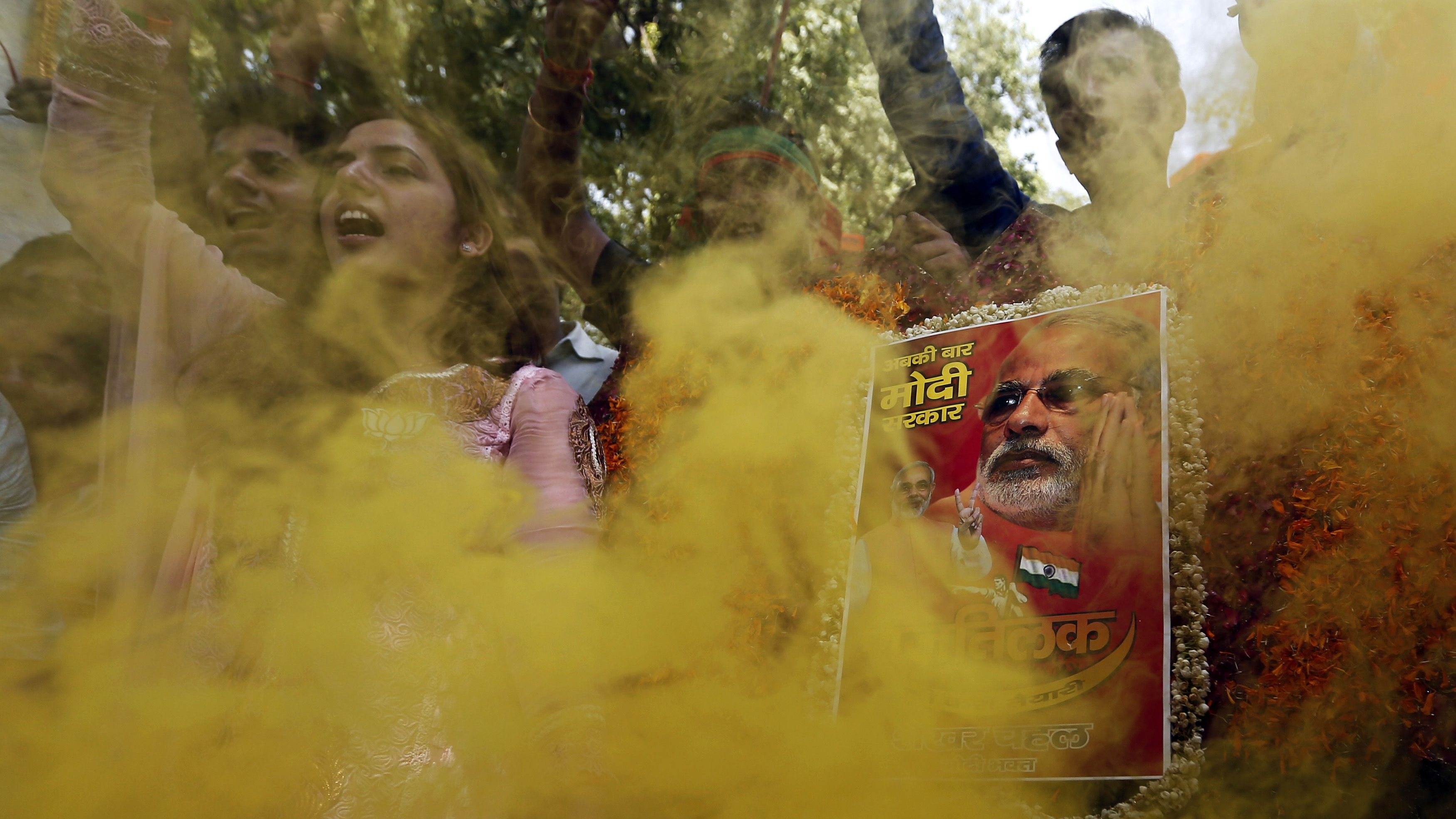 Supporters of India's Bharatiya Janata Party (BJP) hold a portrait of Hindu nationalist Narendra Modi, the prime ministerial candidate for BJP, during celebrations outside the party headquarters in New Delhi May 16, 2014. Opposition candidate Modi will be the next prime minister of India, with early election results on Friday showing the pro-business Hindu nationalist and his party headed for the biggest victory the country has seen in 30 years. REUTERS/Adnan Abidi (INDIA - Tags: POLITICS ELECTIONS TPX IMAGES OF THE DAY) - RTR3PEVY