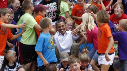 DATE IMPORTED:August 14, 2011Children from public schools in the town of Chatfield, Minnesota, help U.S. President Barack Obama get up after he posed with them for a picture, during his bus trip to the Midwest August 15, 2011. Obama blasted Republicans over taxes on Monday as he launched a bus tour of the U.S. Midwest to tout his job-growth strategy and distance himself from anger toward Washington that could dent his 2012 re-election hopes. Obama is traveling on a bus tour through Minnesota, Iowa and Illinois. REUTERS/Jason Reed