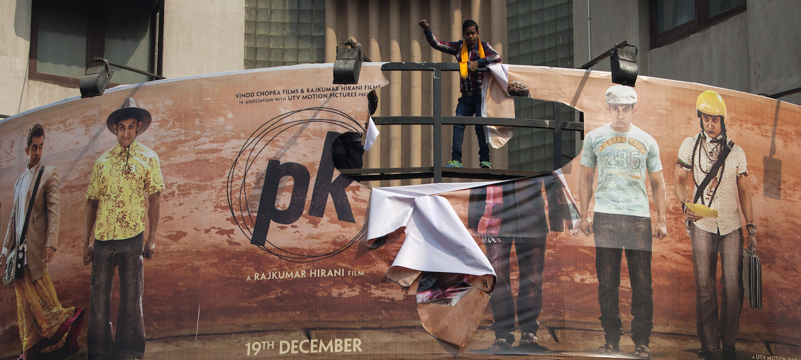"""Hindu right-wing activists of the Hindu Sena tear a giant movie poster during a protest demanding a ban on the Bollywood movie """"PK"""" in New Delhi, India, Tuesday, Dec. 30, 2014."""