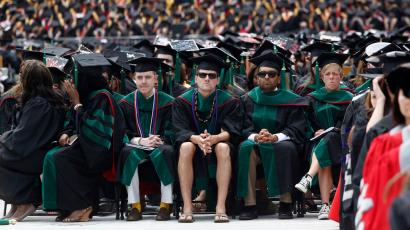 A student in flip flops and shorts (C) watches as U.S. President Barack Obama (not pictured) receives an honorary degree during the spring commencement ceremony at Ohio State University in Columbus, May 5, 2013. REUTERS/Jason Reed (UNITED STATES - Tags: POLITICS EDUCATION SOCIETY TPX IMAGES OF THE DAY) - RTXZBLI