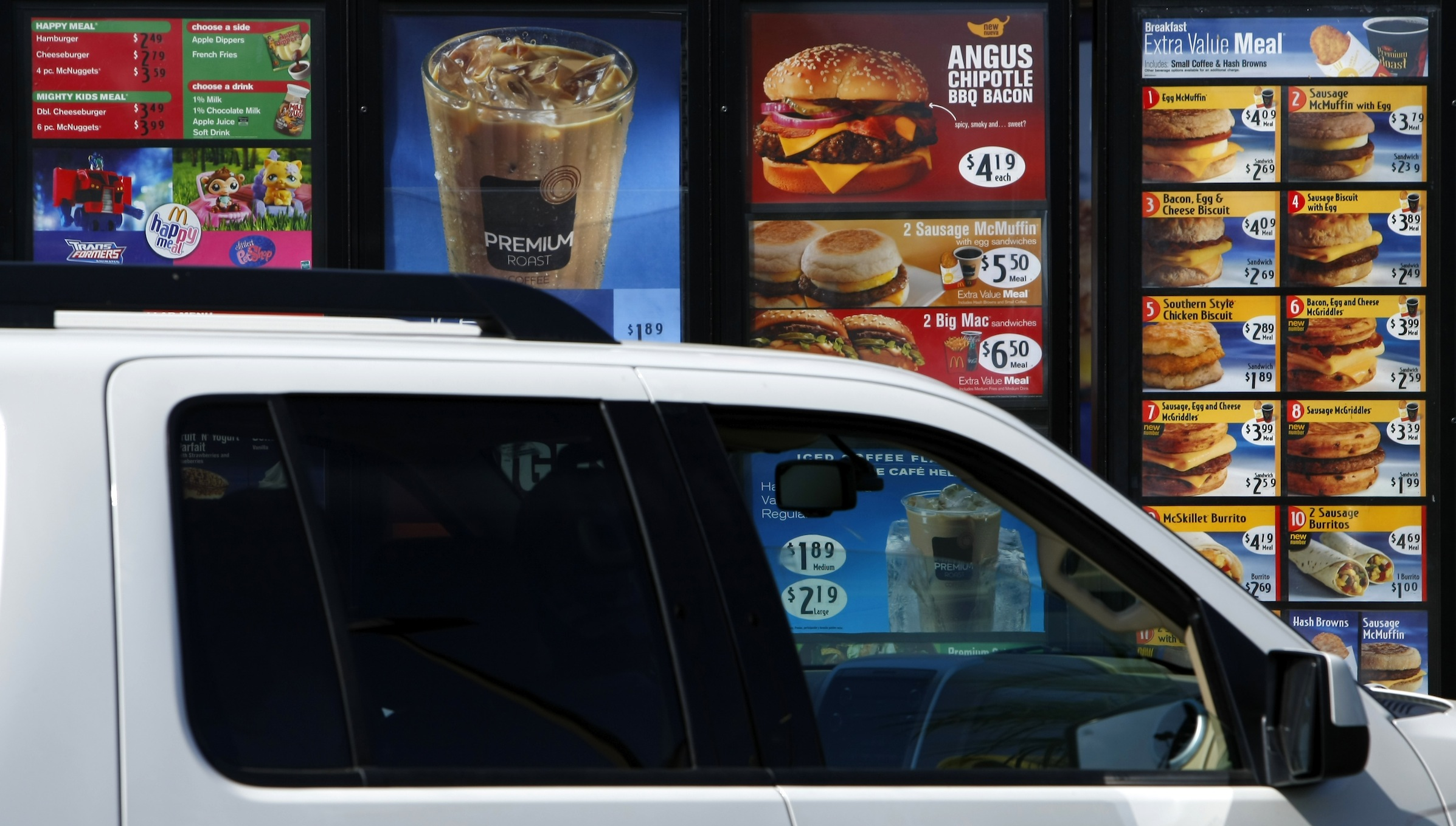 A customer orders food from a drive-thru menu is at a McDonald's restaurant in Encinitas, California July 21, 2008. McDonald's, the world's biggest restaurant chain, reports second-quarter earnings later this week. Investors will be looking for how the company is controlling rising commodity prices. REUTERS/Mike Blake (UNITED STATES) - RTR20EH3
