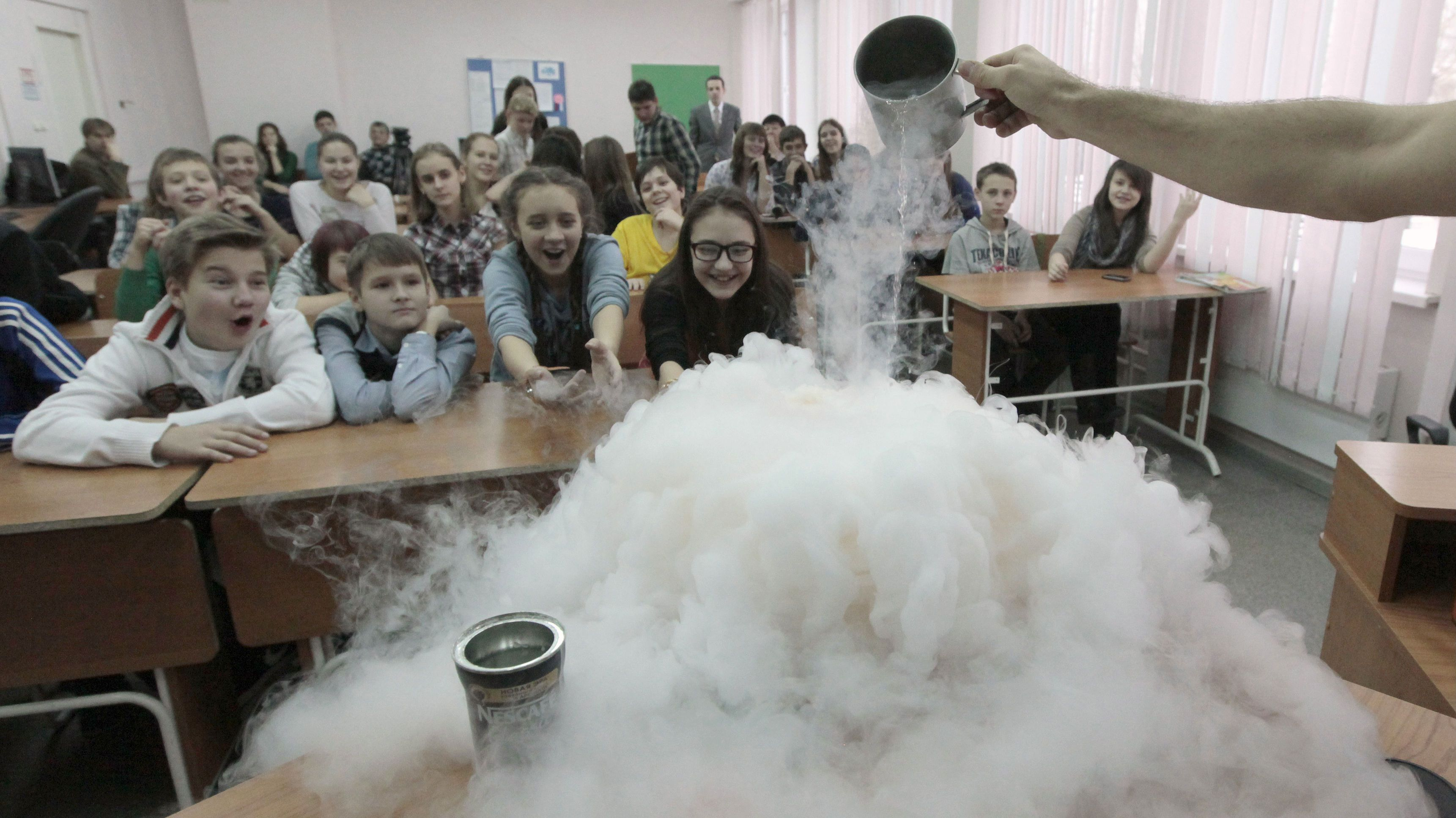 """Pupils watch the effect produced by liquid nitrogen during a demonstration at a local grammar school in Russia's Siberian city of Krasnoyarsk, November 21, 2012. Ivan Timofeenko and Pavel Pankin, students from the Siberian Federal University, specialize in applied mathematics and physics and have conducted experiments aimed at the popularization of the exact sciences, for the pupils of the 7th grade at the """"Universe"""" grammar school. Demonstrative and spectacular lessons, dedicated to chemical, physical, chemical-biological and physical-chemical experiments, are expected to be held at 10 comprehensive schools of Krasnoyarsk in order to select most talented and enthusiastic schoolchildren for facultative training at the university starting from February 2013, according to organizers. REUTERS/Ilya Naymushin (RUSSIA - Tags: EDUCATION SCIENCE TECHNOLOGY SOCIETY)"""