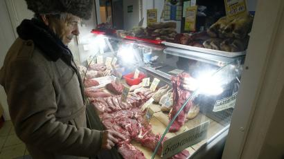 A man looks at meat on offer on a market stall in Moscow.