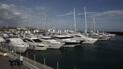 Cyclists look at boats in a marina near Limassol, a coastal town in southern Cyprus.