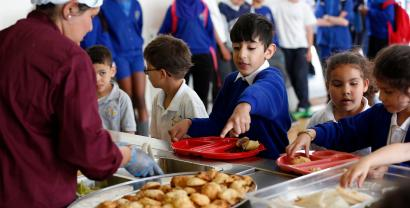 Students receive their lunch at Salusbury Primary School in northwest London June 11, 2014. This September, a new government scheme plans to give free meals to all reception, year 1 and 2 students registered in England's state-funded schools. Local media reports that this will amount to saving families about ?400 a year per child. REUTERS/Suzanne Plunkett (BRITAIN - Tags: EDUCATION SOCIETY FOOD) - RTR3T86S