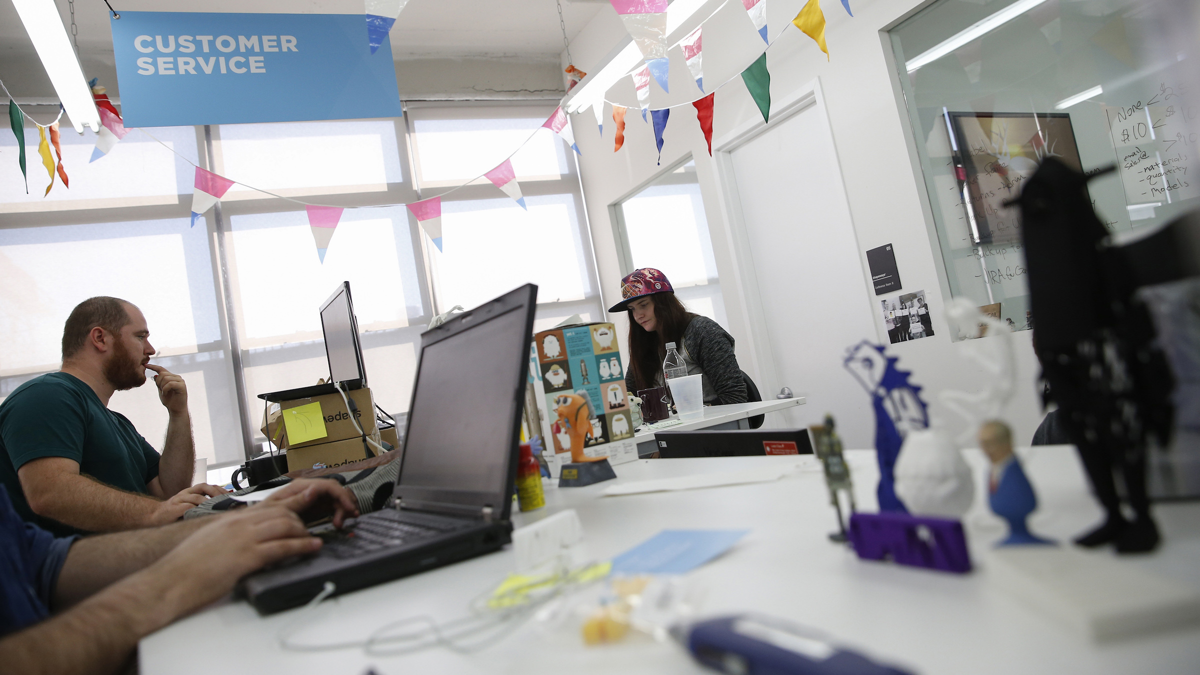 People work at the customer service area inside the Shapeways 3D printing office in the borough of Queens in New York, September 17, 2014. Shapeways is  a young Dutch 3D printing firm that has two factories, one in Eindhoven in the Netherlands and one in New York, that let anyone - from haute-couture designers to cat-lovers - print what they want. CEO Peter Weijmarshausen moved the firm's headquarters to New York in 2010 to be close to tis main market and attract talent and investment.  To match Insight EUROPE-STARTUPS/MAKERS  Picture taken September 17, 2014. REUTERS/Shannon Stapleton (UNITED STATES - Tags: BUSINESS SCIENCE TECHNOLOGY) - RTR46Y1I