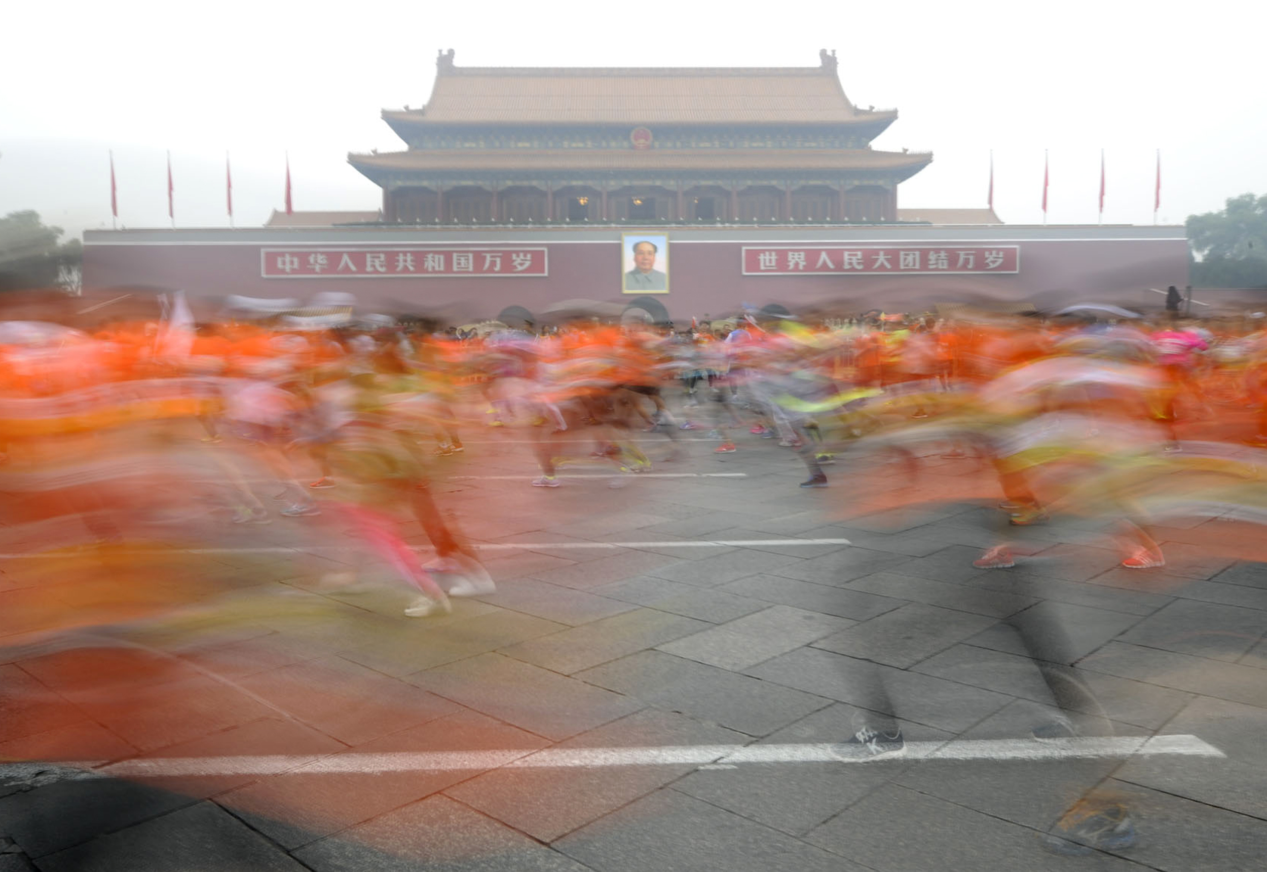 Participants run past the Tiananmen gate with a portrait of China's late leader Mao Zedong during a hazy day at the Beijing International Marathon, Beijing October 19, 2014. REUTERS/Stringer