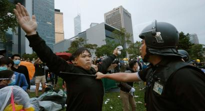 A pro-democracy protester blocks a riot policeman during a clash outside the government headquarters in Hong Kong December 1, 2014. Hong Kong police baton-charged and pepper-sprayed thousands of pro-democracy demonstrators in the early hours of Monday who were trying to encircle government headquarters, defying orders to retreat after more than two months of protests. REUTERS/Bobby Yip (CHINA - Tags: POLITICS BUSINESS EDUCATION CRIME LAW TPX IMAGES OF THE DAY) - RTR4G6F4