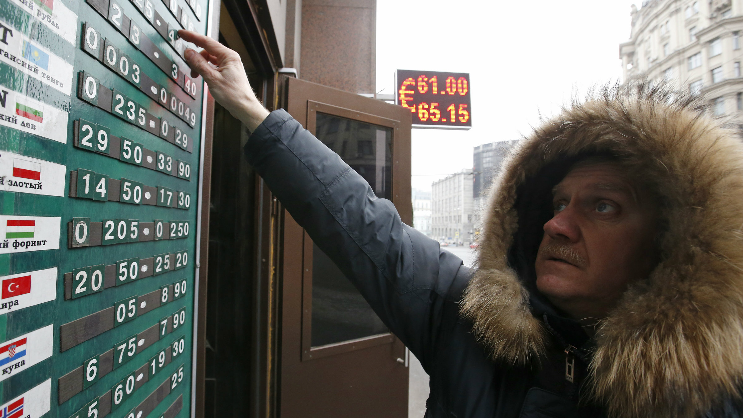An employee changes figures on a board showing currency exchange rates in Moscow.