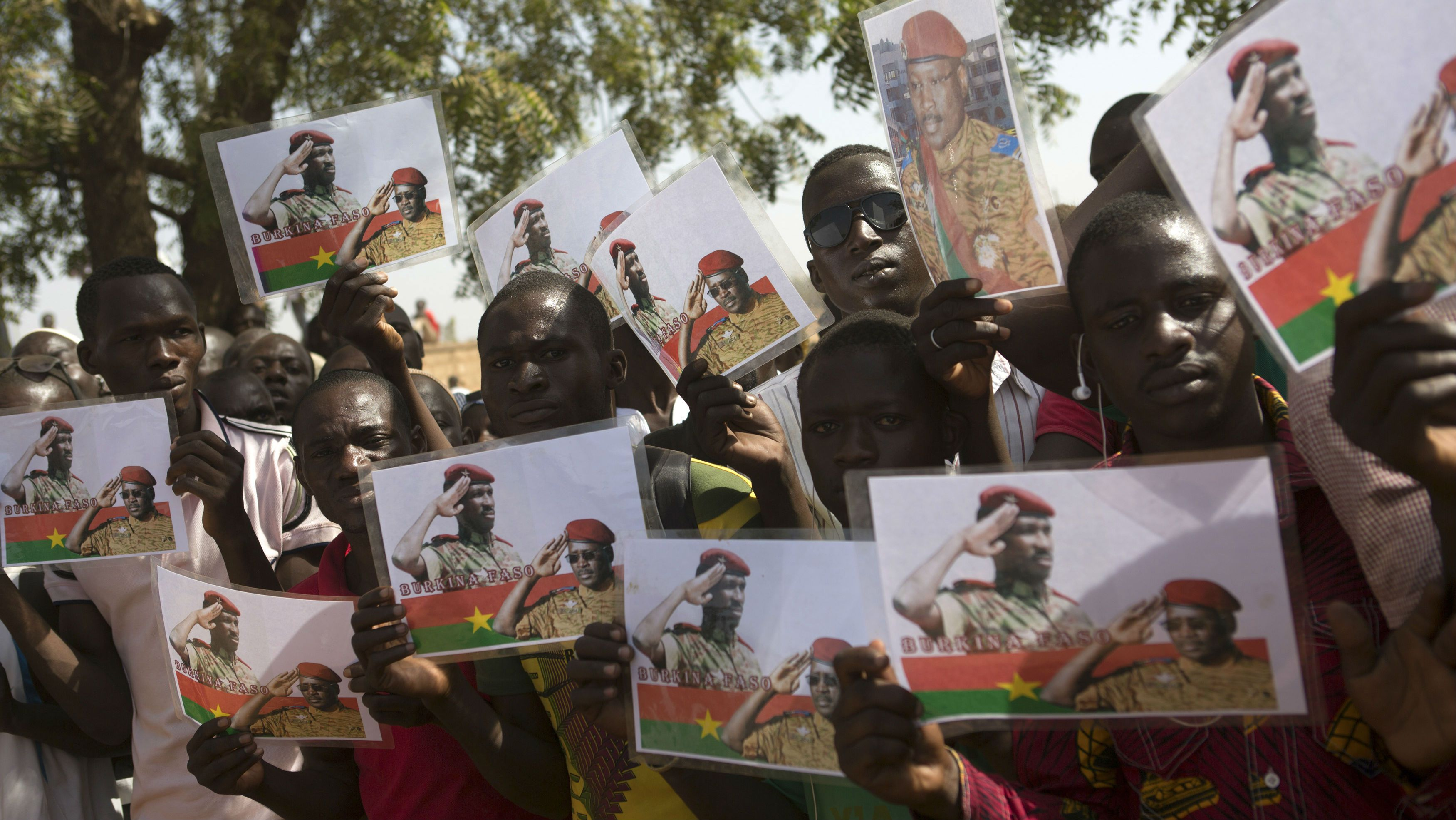 People hold pictures showing former president Thomas Sankara and Prime Minister Isaac Zida during a funeral service for six people killed during the popular uprising of October 30 and 31 in Ouagadougou, December 2, 2014. REUTERS/Joe Penney (BURKINA FASO - Tags: POLITICS OBITUARY CIVIL UNREST SOCIETY)