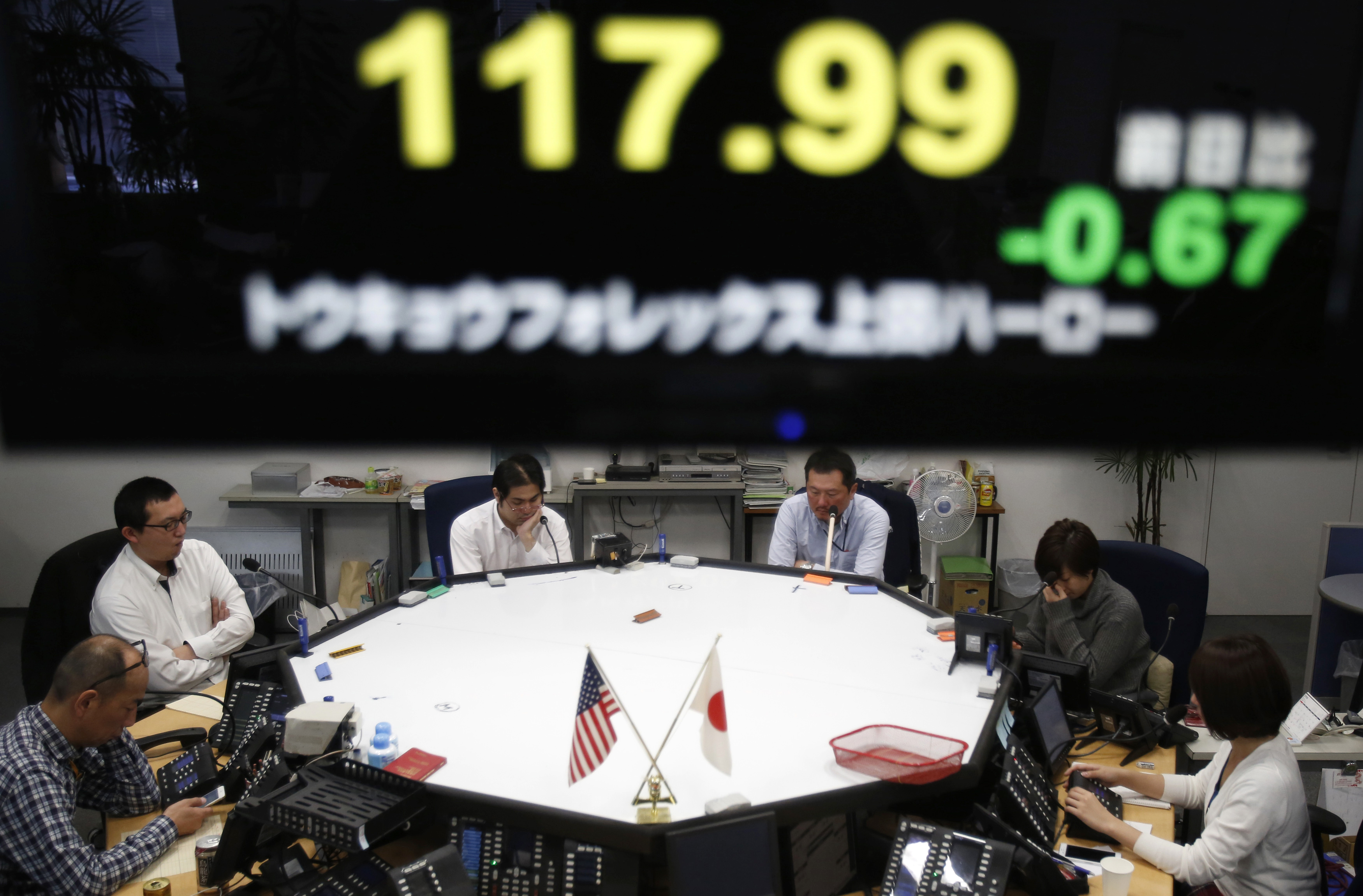 Employees of a foreign currency company work in a dealing room in Tokyo.