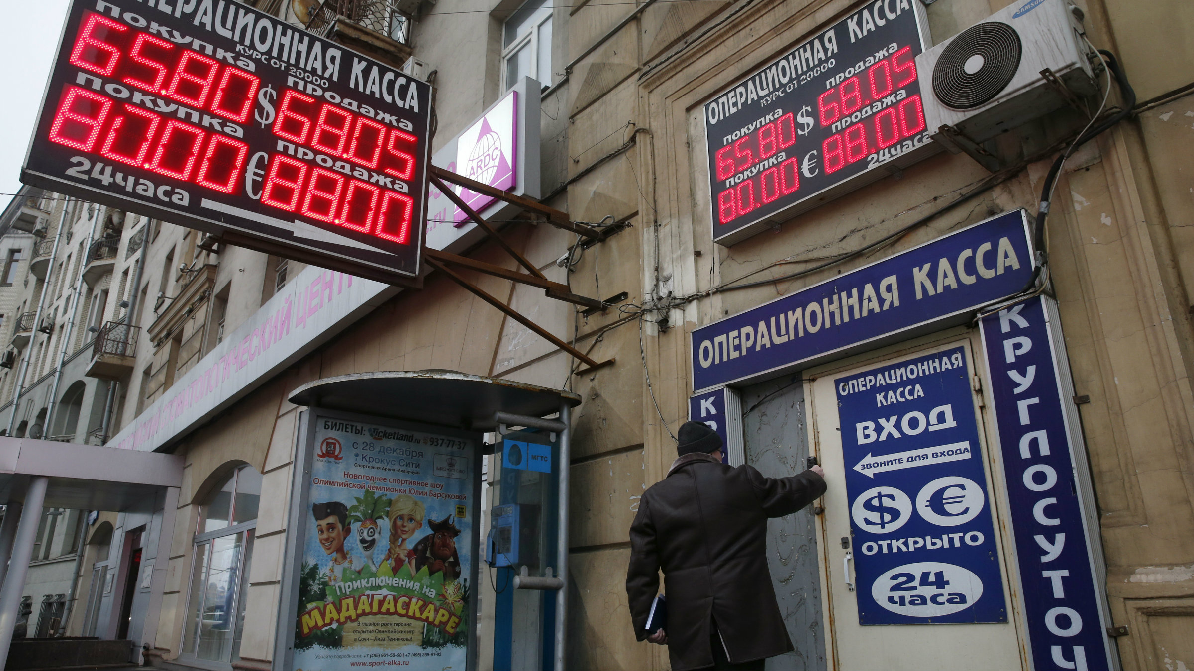 A man walks past a building and a board showing currency exchange rates in Moscow.