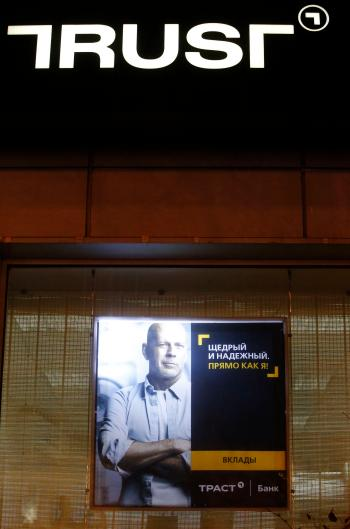 An advertisement for Trust Bank, featuring an image of Hollywood actor Bruce Willis, is on display outside a bank branch in Moscow, December 22, 2014. Russian mid-sized lender Trust Bank is to receive up to 30 billion roubles ($530 million) from the central bank to stop it going bankrupt in the first bailout of its kind during the current rouble crisis. Trust, which hired actor Bruce Willis as the face of a major advertising campaign, is Russia's 32nd largest lender by assets, according to Interfax data. It is the 15th biggest by private personal accounts, including deposits. REUTERS/Sergei Karpukhin (RUSSIA - Tags: BUSINESS) - RTR4IZ3E