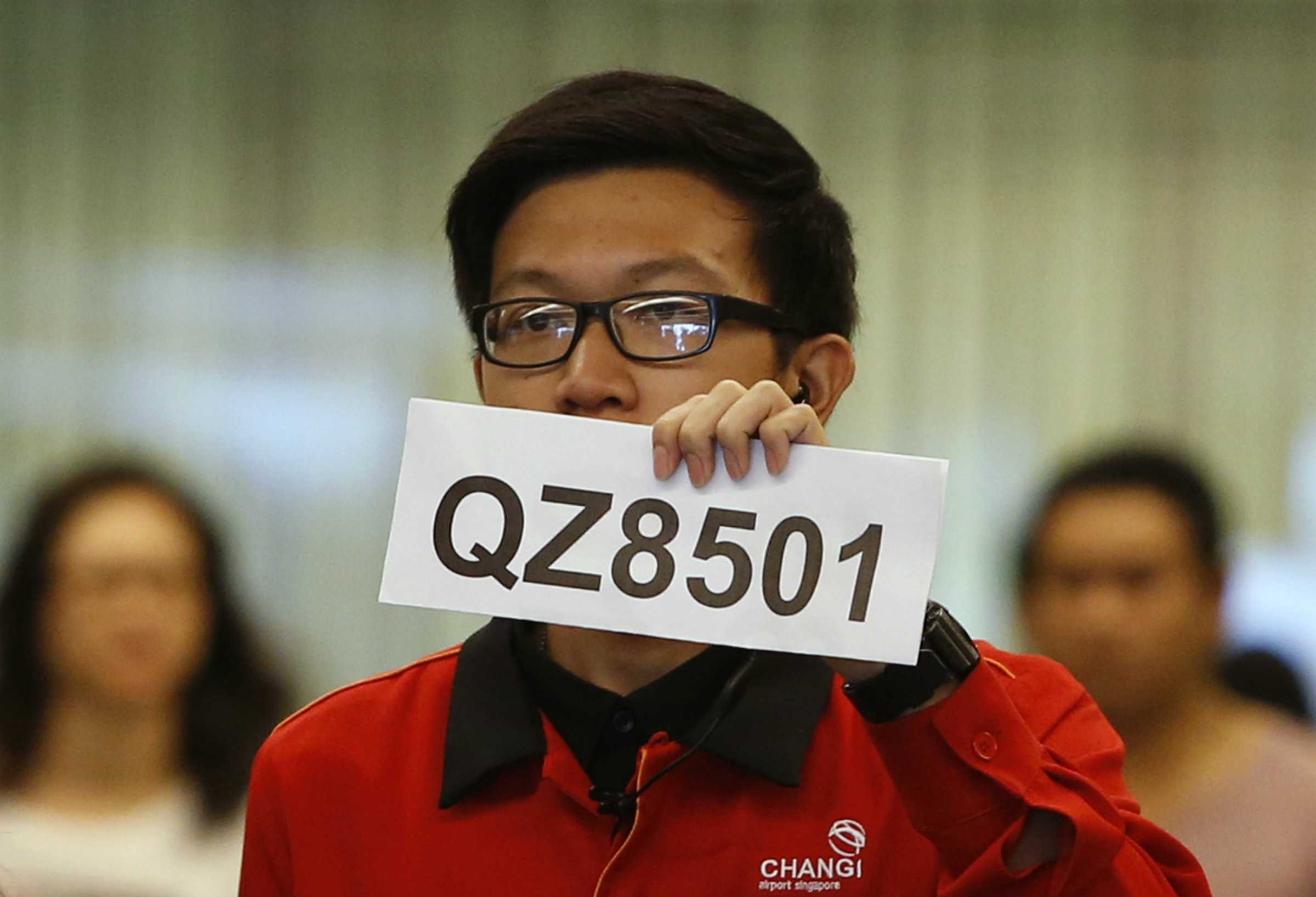 DATE IMPORTED: December 28, 2014 A Changi Airport staff holds up a sign to direct possible next-of-kins of passengers of AirAsia flight QZ 8501 from Indonesian city of Surabaya to Singapore, at Changi Airport in Singapore December 28, 2014. Indonesia's Transport Ministry official Hadi Mustofa said the aircraft, flight number QZ 8501, lost contact with the Jakarta air traffic control tower on Sunday at 6:17 a.m local time (2317 GMT). The Airbus 320-200 had 155 passengers and crew on board, another Indonesian Transport official said. REUTERS/Edgar Su (SINGAPORE - Tags: ENVIRONMENT SOCIETY TRANSPORT)
