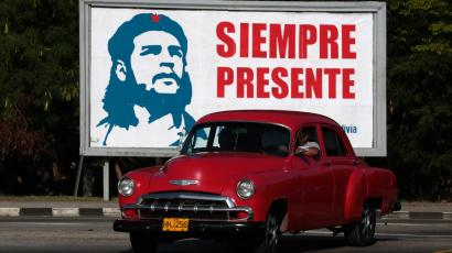 A car is driven beside a billboard with the image of revolutionary leader Guevara in Havana