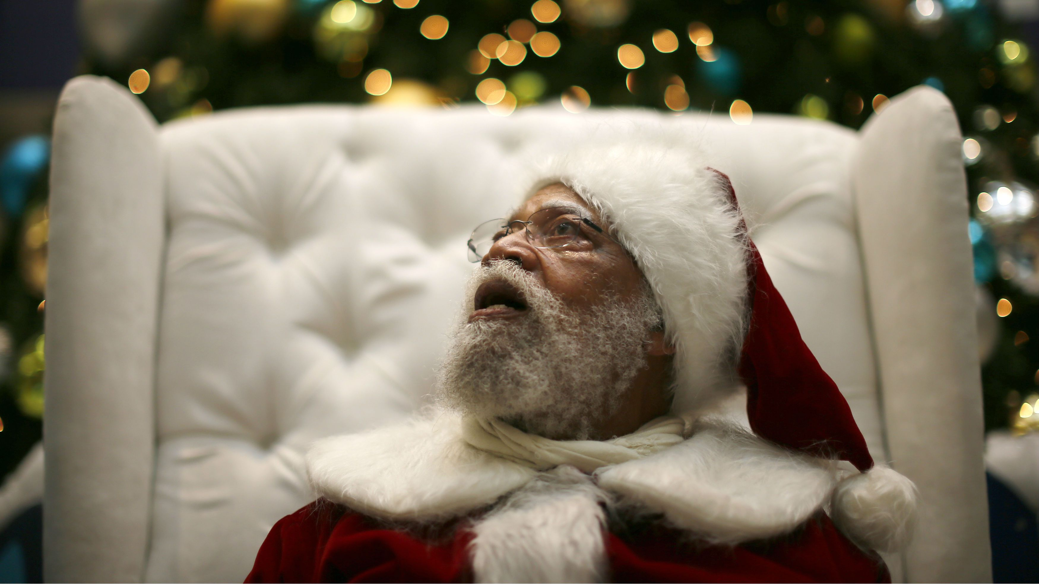 African American Santa Claus Langston Patterson, 77, waits for children to arrive at Baldwin Hills Crenshaw Plaza mall in Los Angeles, California, December 16, 2013. Patterson has worked as Santa since 2004 at the mall, which is one of the few in the country with a black Santa Claus. A New Mexico teacher who told an African American student that Santa Claus was white has been put on paid administrative leave, an official said on Monday. REUTERS/Lucy Nicholson