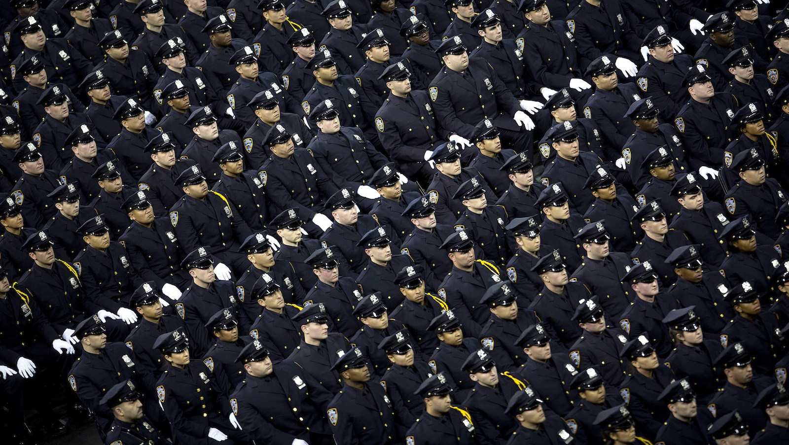 New York Police Department graduates attend their induction ceremony at Madison Square Garden in New York, December 27, 2013. The NYPD graduated 1171 recruits to ranks of police officer. REUTERS/Carlo Allegri (UNITED STATES - Tags: SOCIETY TPX IMAGES OF THE DAY) - RTX16V9L