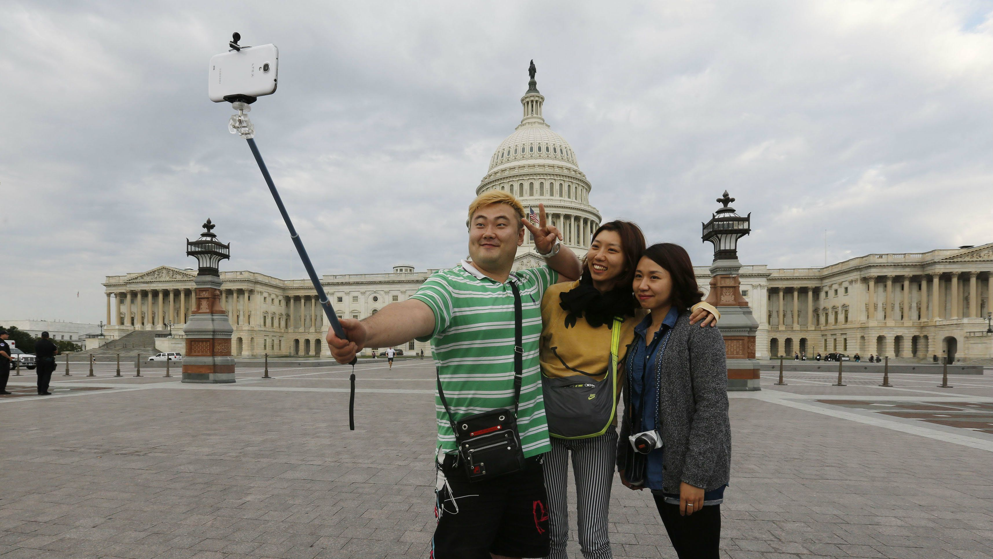 South Korean tourists (L-R) Heemok Ann, Eunyi Ji, and Mijung Jung take their own picture in front of the U.S. Capitol dome on Capitol Hill in Washington.