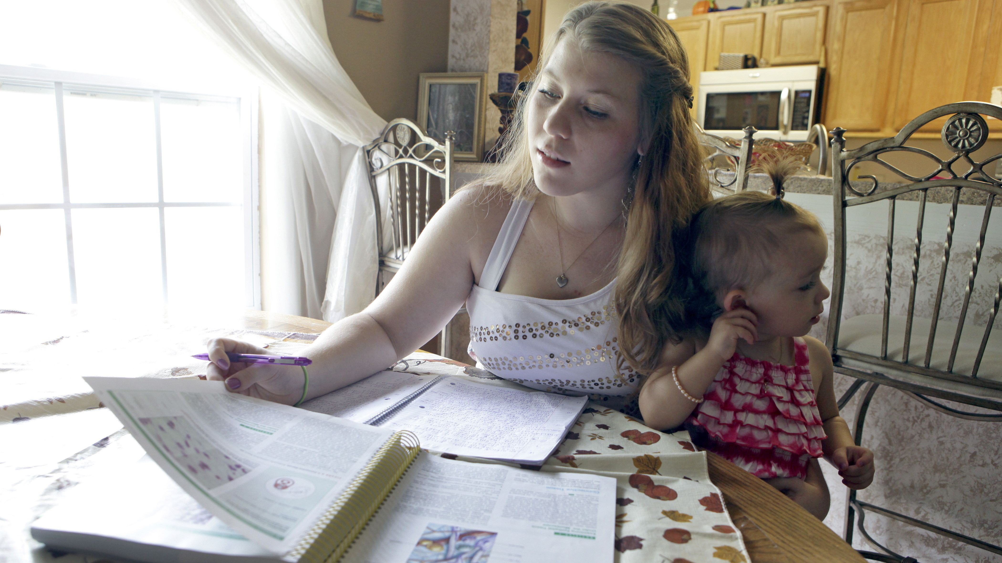 In this Monday, Sept. 10, 2012 photo, Kali Gonzalez, a student at St. John's State College studies while holding her daughter Kiah, 2, at their home in St. Augustine, Fla. A new report by the National Women's Law Center says offering pregnant teens extra support would ultimately save taxpayers money by helping them become financially independent and not dependent on welfare.(AP Photo/John Raoux)