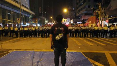 A pro-democracy protester stands in front of a line of riot police at Mongkok shopping district in Hong Kong early