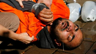 Demonstrator Maboud Ebrahimzadeh lies on the pavement after his ordeal in a simulation of waterboarding outside the Justice Department in Washington November 5, 2007. The confirmation of Bush nominee Michael Mukasey as attorney general is in jeopardy after his refusal to state whether the interrogation technique known as waterboarding violates U.S. laws banning torture. REUTERS/Kevin Lamarque (UNITED STATES) - RTR1VOW6