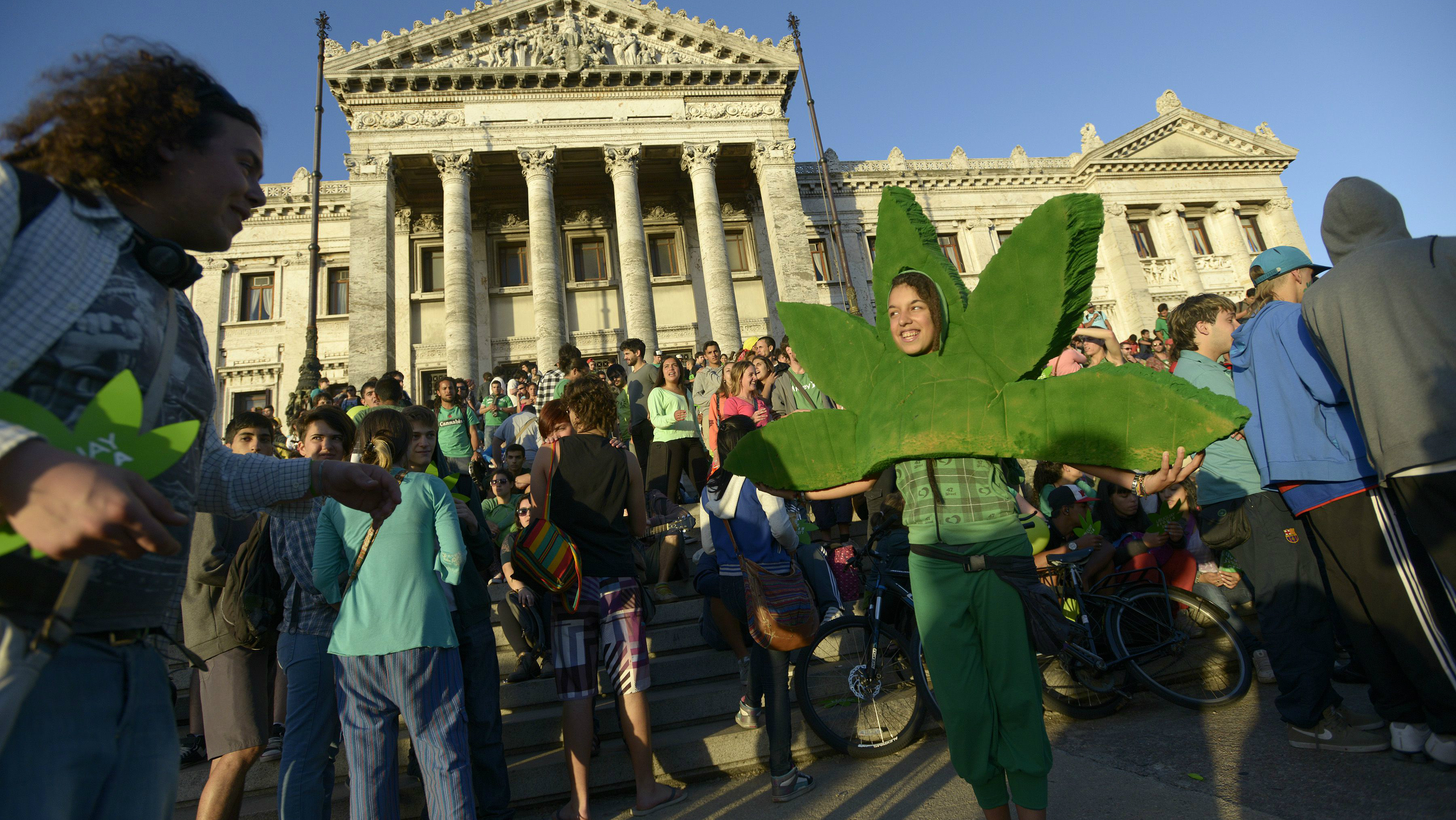 In this Tuesday, Dec. 10, 2013 photo, people attend a demonstration in support of the legalization of marijuana outside the Congress in Montevideo, Uruguay. Uruguay has become the first country to create a national marketplace for legal marijuana, with the government regulating the production, sales and use of pot in a bold bid to control addiction and drug violence. The Senate gave final legislative approval to the bill late Tuesday. (AP Photo/Matilde Campodonico)