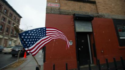 A flag waves in the wind before an AT&T holiday gifting event for wounded veterans in East Boston, Mass. Thursday, Dec. 11, 2014. (Gretchen Ertl/AP Images for AT&T)