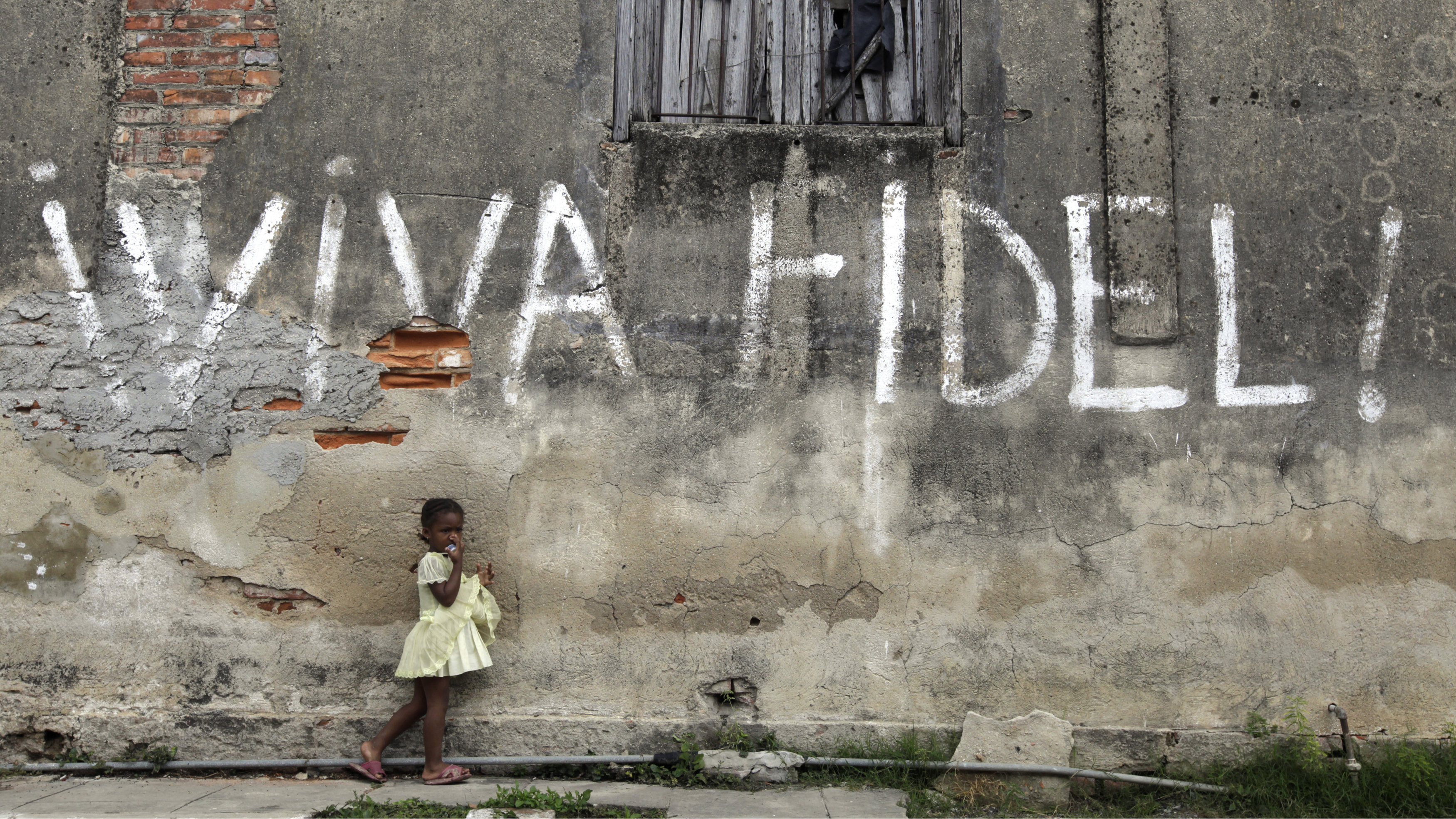 """A girl stands next to graffiti that reads """"Viva Fidel"""" (Long live Fidel), in Cuba's western province of Pinar del Rio February 23, 2010."""
