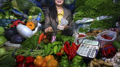 woman with vegetables and money