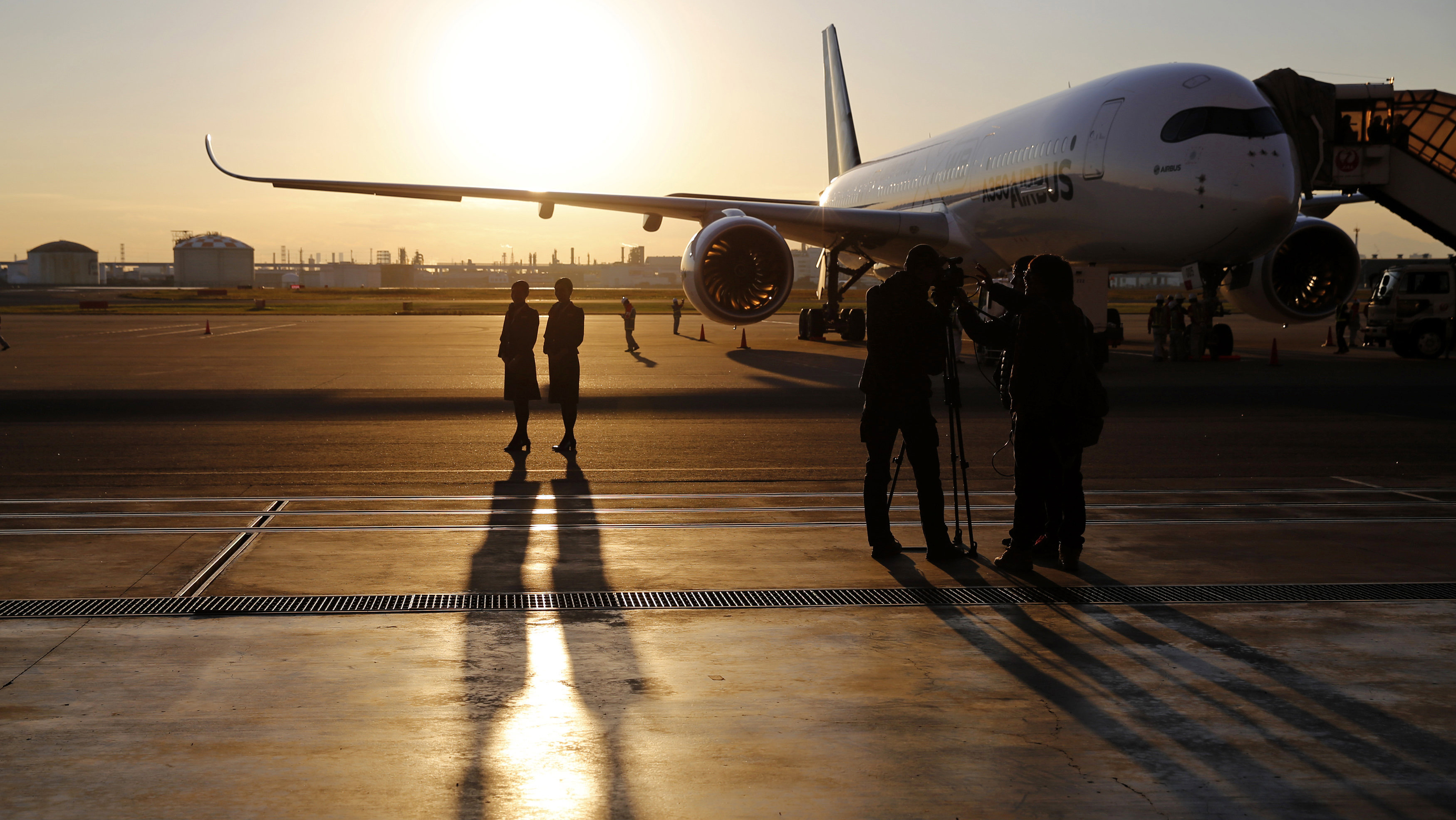 Cabin attendants from Japan Airlines (JAL) pose for the media in front of an Airbus A350 XWB aircraft after it landed for its market survey at Haneda airport in Tokyo November 19, 2014. JAL placed a major order with Airbus for 31 A350 XWBs, which are scheduled for delivery to JAL from 2019, according to Airbus press release. The A350 is Airbus's newest plane.