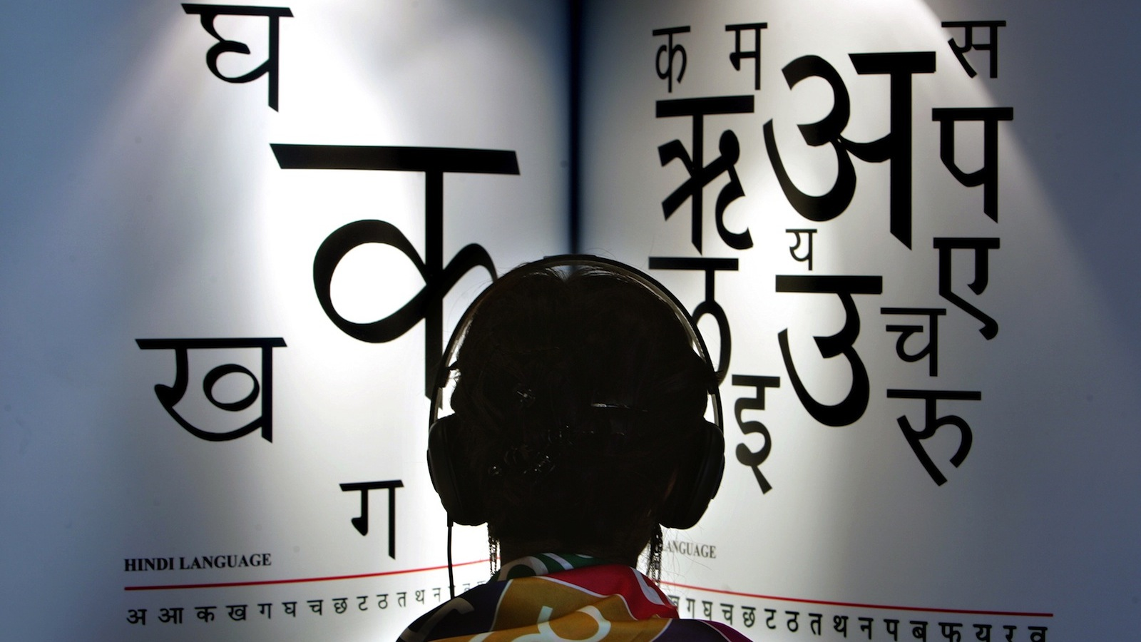 A woman listens to explanations on headphones about the Indian languages Hindi, left, and Marathi at the International Book Fair in Frankfurt, central Germany, Wednesday, Oct. 4, 2006. Indian literature, which already has a global following for its English writers, is reaching out to a broader audience for works in dozens of Indian languages at the Frankfurt Book Fair, which opened Tuesday. (AP Photo/Michael Probst)