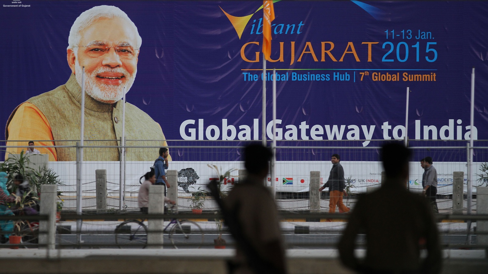Indian policemen stand guard as people walk past a hoarding with a portrait of Indian Prime Minister Narendra Modi, advertising the Vibrant Gujarat Summit 2015 in Gandhinagar, India, Friday, Jan. 9, 2015. U.S. Secretary of State John Kerry is scheduled to attend the three-day summit that starts Sunday. (AP Photo/ Ajit Solanki)