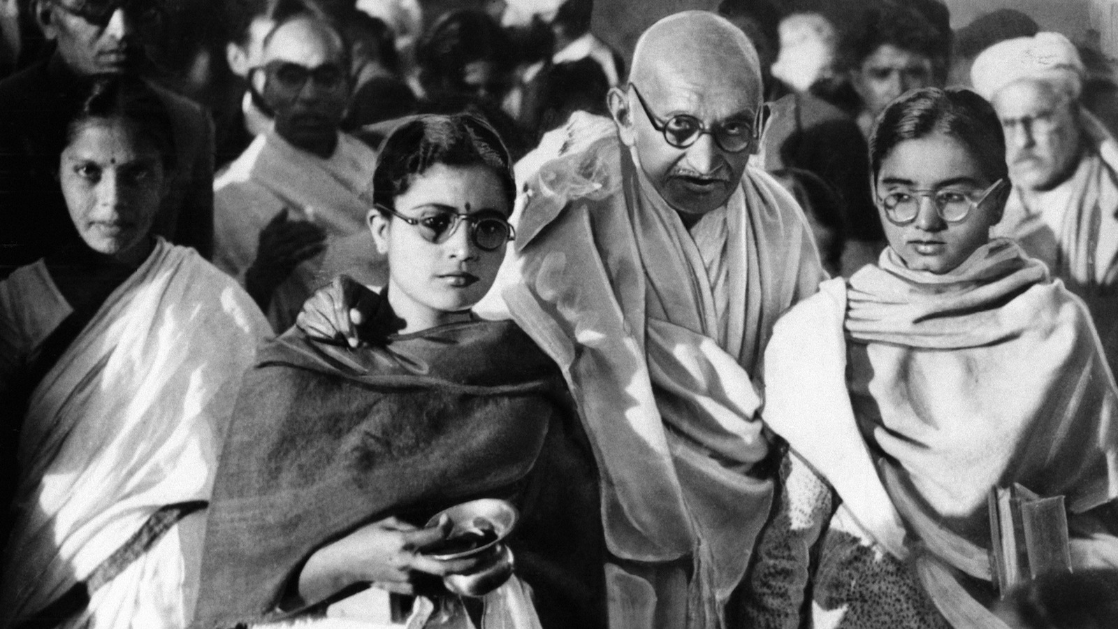 Mahatma Gandhi resting arms on shoulders of two disciples, one of whom carries brass bowl of holy water, glances sharply at cameraman January 1948. Gandhi dislikes being photographed and declines permit use of flash bulbs which hurt his eyes. (AP Photo)