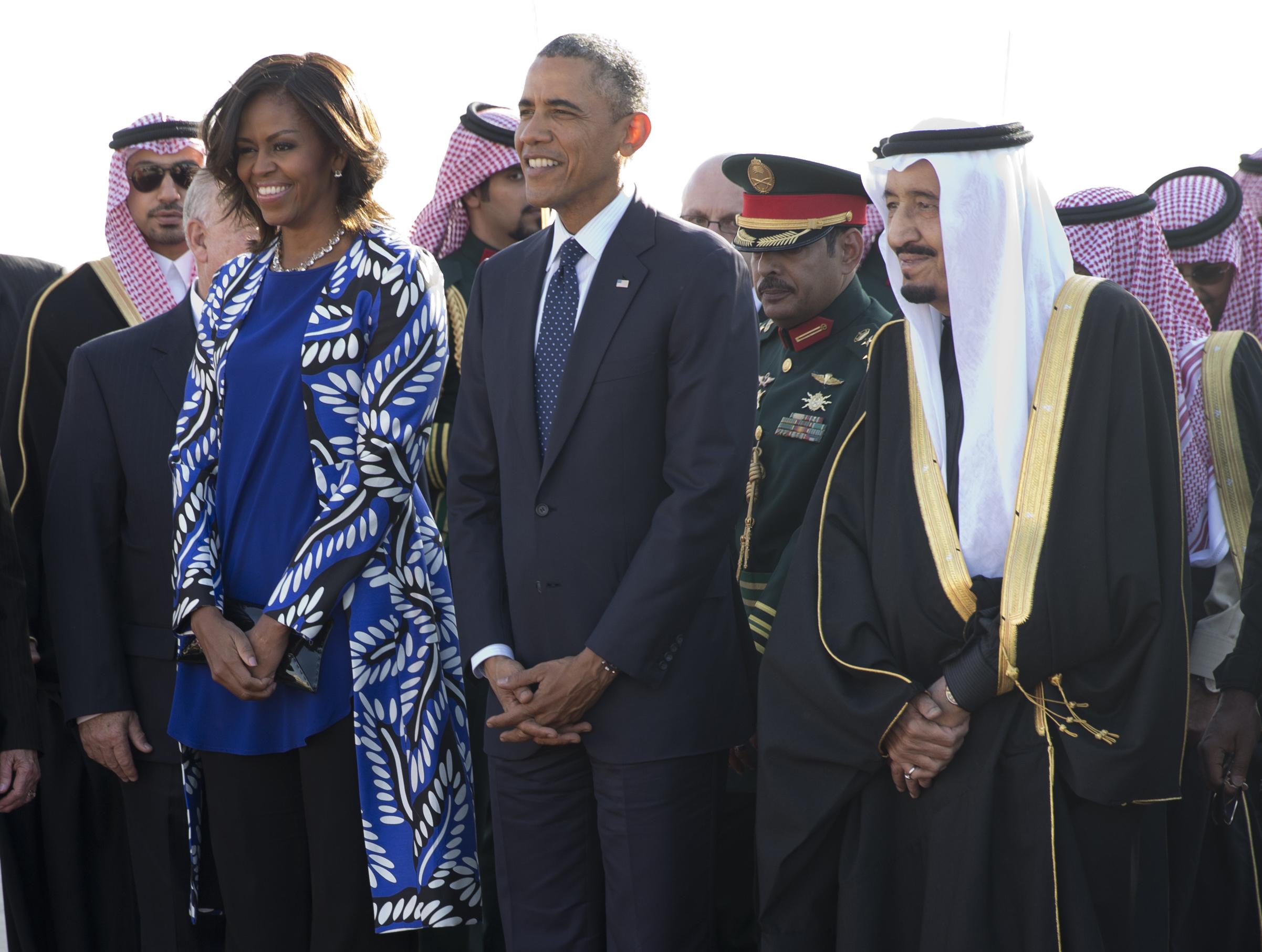 President Barack Obama and first lady Michelle Obama stand with new Saudi King Salman bin Abdul Aziz they arrive on Air Force One at King Khalid International Airport, in Riyadh, Saudi Arabia, Tuesday, Jan. 27, 2015. (AP Photo/Carolyn Kaster)
