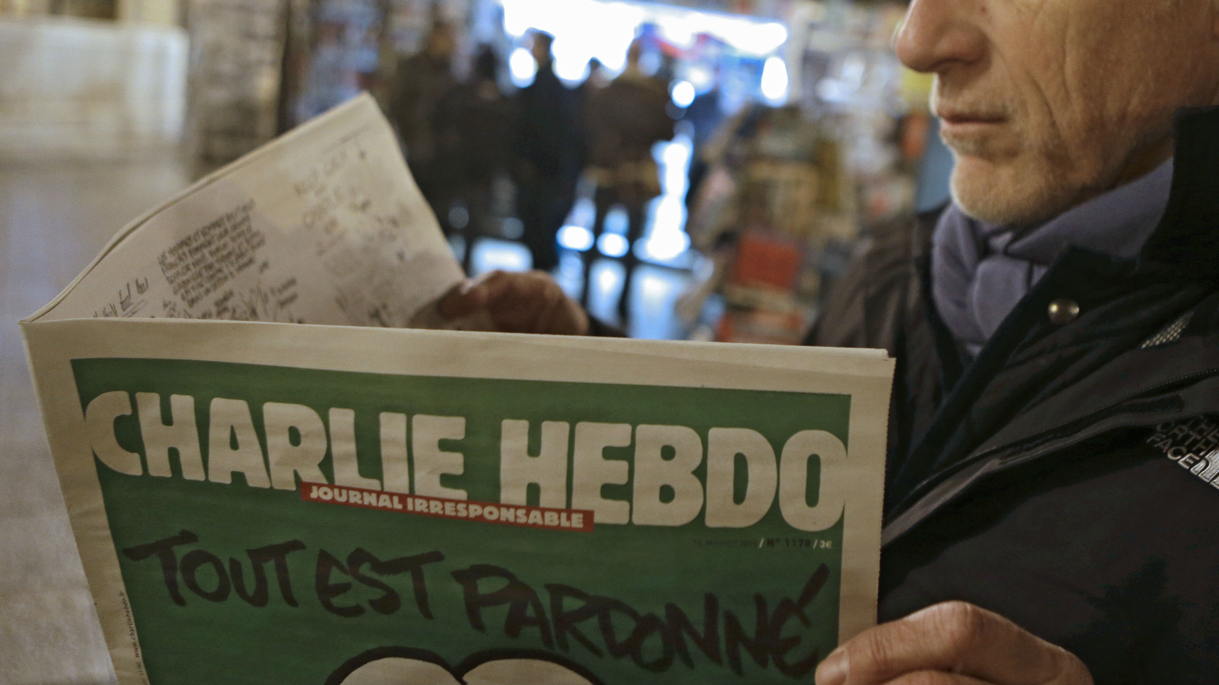 """Jean Paul Bierlein reads the latest issue of Charlie Hebdo outside a newsstand in Nice, southeastern France, Wednesday, Jan. 14, 2015. In an emotional act of defiance, Charlie Hebdo resurrected its irreverent and often provocative newspaper, featuring a caricature of the Prophet Muhammad on the cover that drew immediate criticism and threats of more violence. The black letters on the front page read: """"All is forgiven."""" (AP Photo/Lionel Cironneau)"""