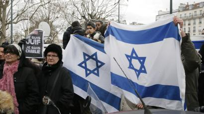 People wave Israeli flags after Israeli Prime Minister Benjamin Netanyahu's visit to the kosher market where four hostages were killed, in Paris, France, Monday, Jan. 12, 2015.