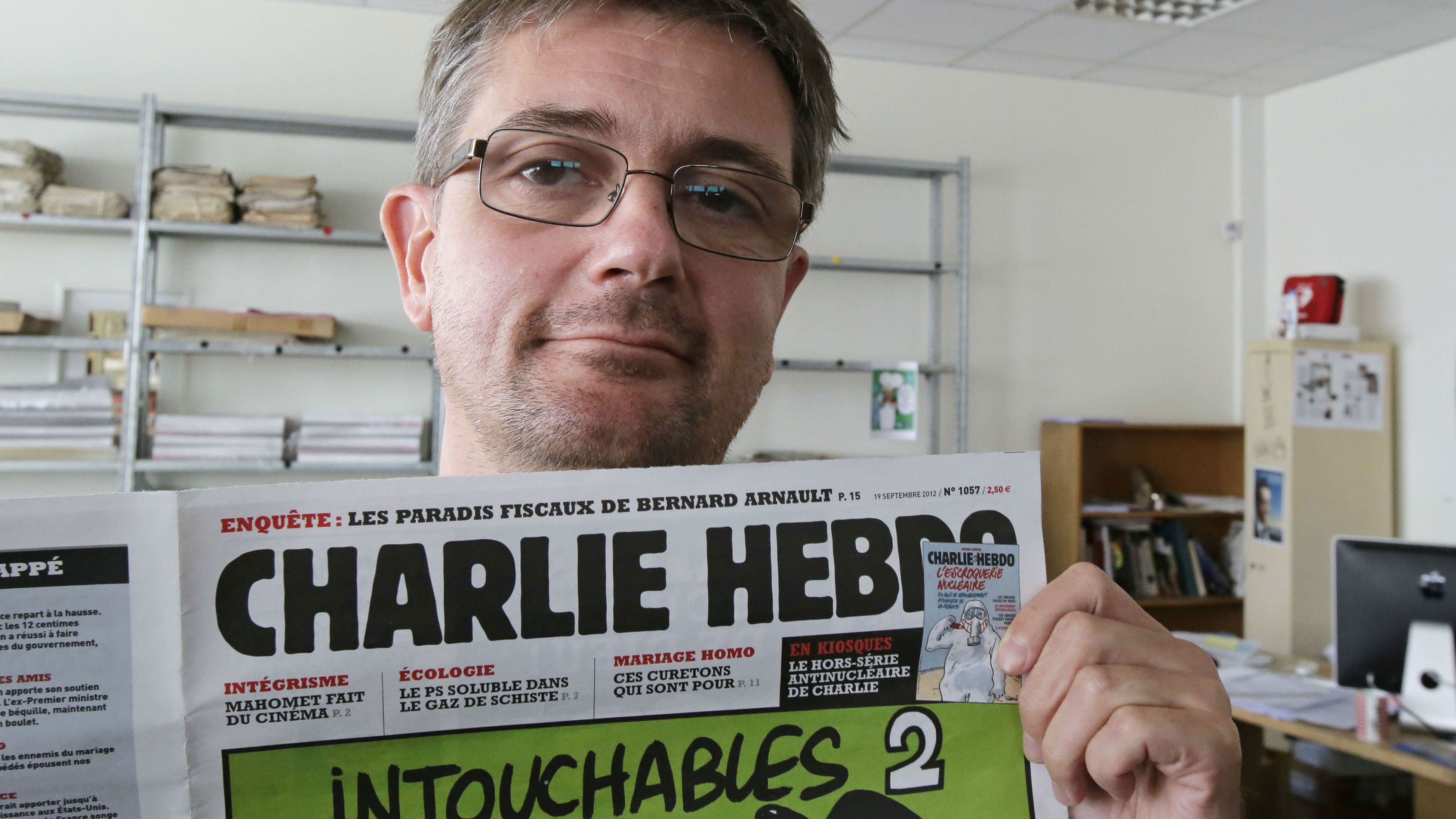 "Publishing director of the satyric weekly Charlie Hebdo, Charb, displays the front page of the newspaper as he poses for photographers in Paris, Wednesday, Sept. 19, 2012. Police took up positions outside the Paris offices of the satirical French weekly that published crude caricatures of the Prophet Muhammad on Wednesday that ridicule the film and the furor surrounding it. The provocative weekly, Charlie Hebdo, was firebombed last year after it released a special edition that portrayed the Prophet Muhammad as a ""guest editor"" and took aim at radical Islam. (AP Photo/MIchel Euler)"