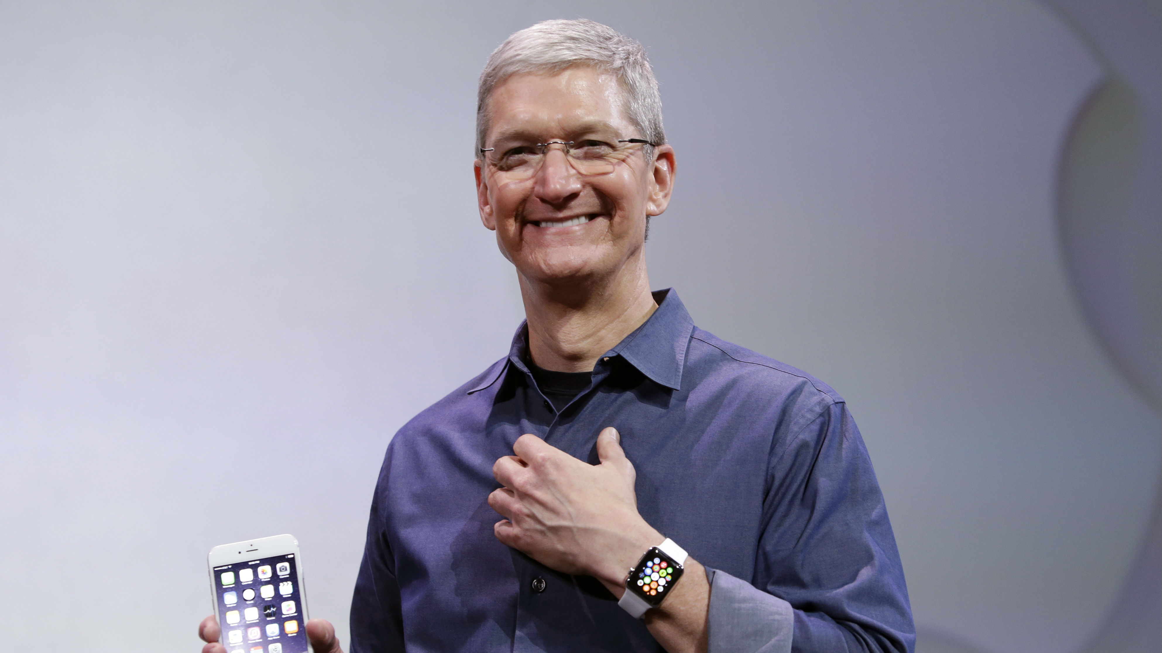 Apple CEO Tim Cook, holding an IPhone 6 Plus, discusses the new Apple Watch and iPhone 6s on Tuesday, Sept. 9, 2014, in Cupertino, Calif. (AP Photo/Marcio Jose Sanchez)