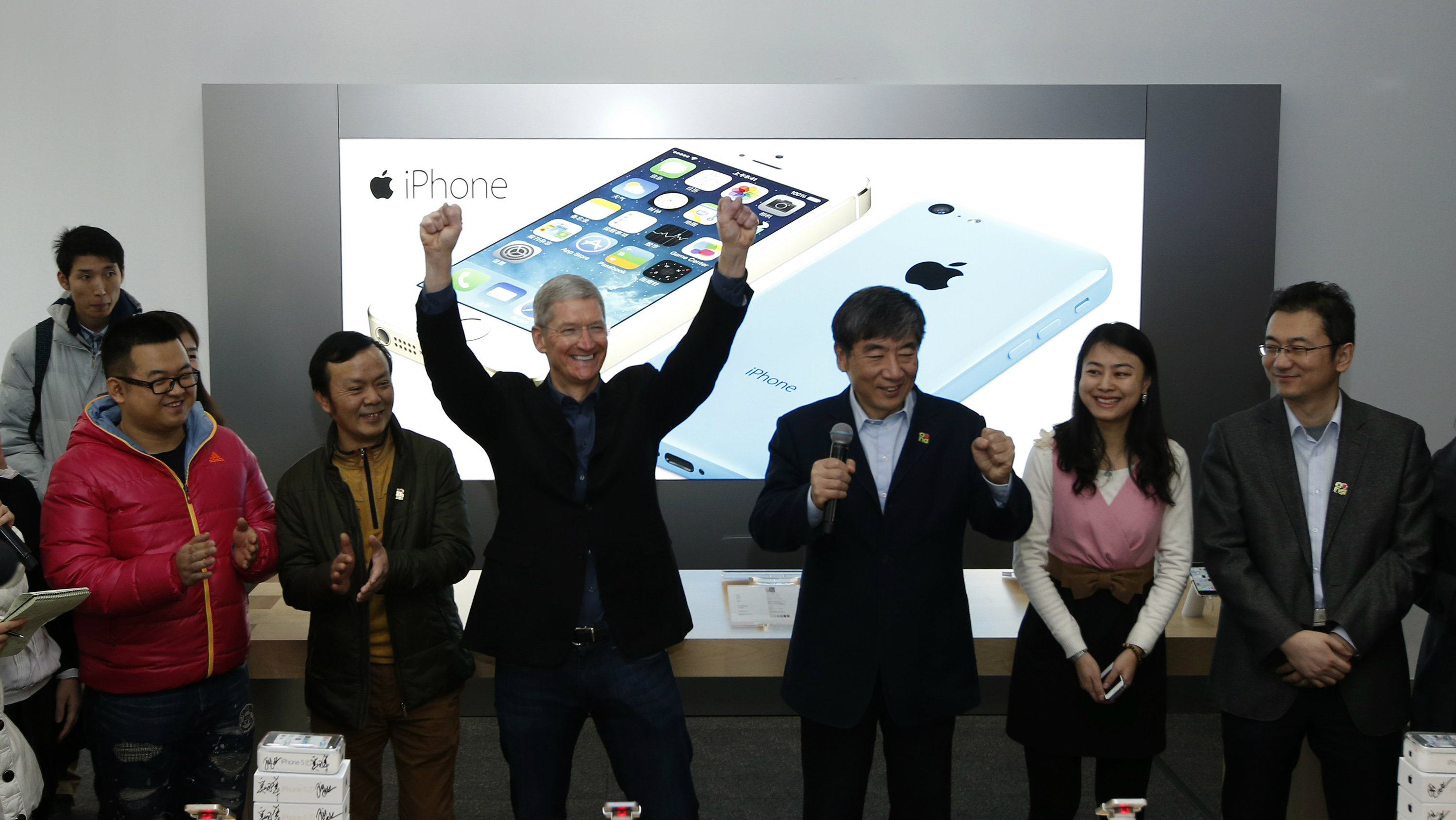 DATE IMPORTED:January 17, 2014Apple Inc.'s CEO Tim Cook (3rd L) reacts next to China Mobile Ltd's Chairman Xi Guohua (3rd R) at an event celebrating the launch of Apple's iPhone on China Mobile's network at a China Mobile shop in Beijing January 17, 2014. Apple Inc is finally launching its iPhone on China Mobile Ltd's vast network on Friday, opening the door to the world's largest carrier's 763 million subscribers and giving its China sales a short-term jolt. REUTERS/
