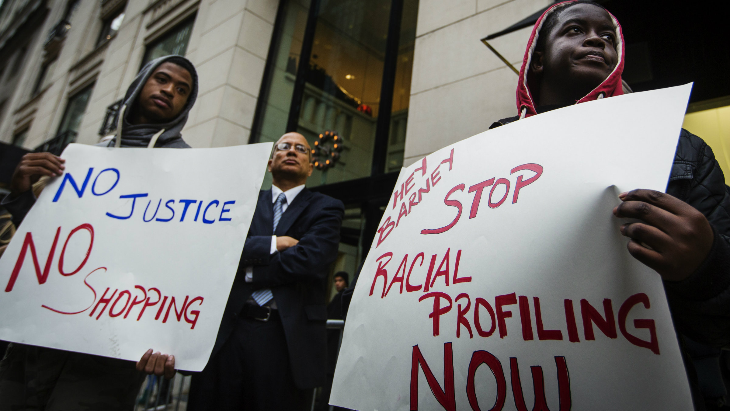 Demonstrators stand in front of a Barneys luxury department store of with signs decrying allegations that Barney's and Macy's stores have unfair security policies aimed at minorities in New York October 30, 2013. Picketers headed for the Manhattan storefront of Barneys New York Inc on Wednesday to express outrage over black customers' complaints that they were stopped by police after making luxury purchases. REUTERS/Lucas Jackson (UNITED STATES - Tags: CIVIL UNREST BUSINESS)