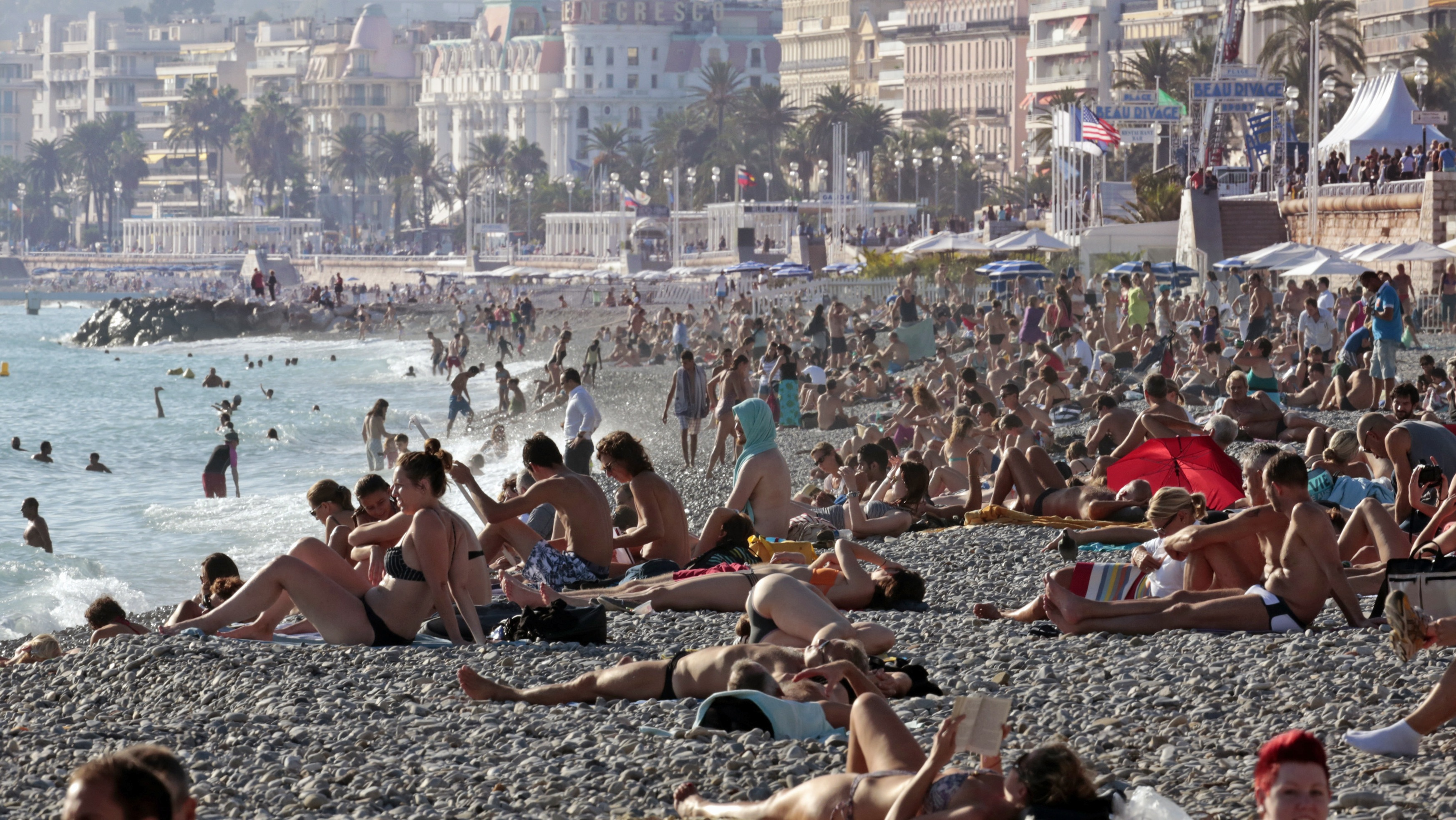 People sunbathe on the beach during an unusually warm and sunny autumn day on the Promenade Des Anglais in Nice, October 18, 2014. REUTERS/Eric Gaillard (FRANCE - Tags: ENVIRONMENT SOCIETY)