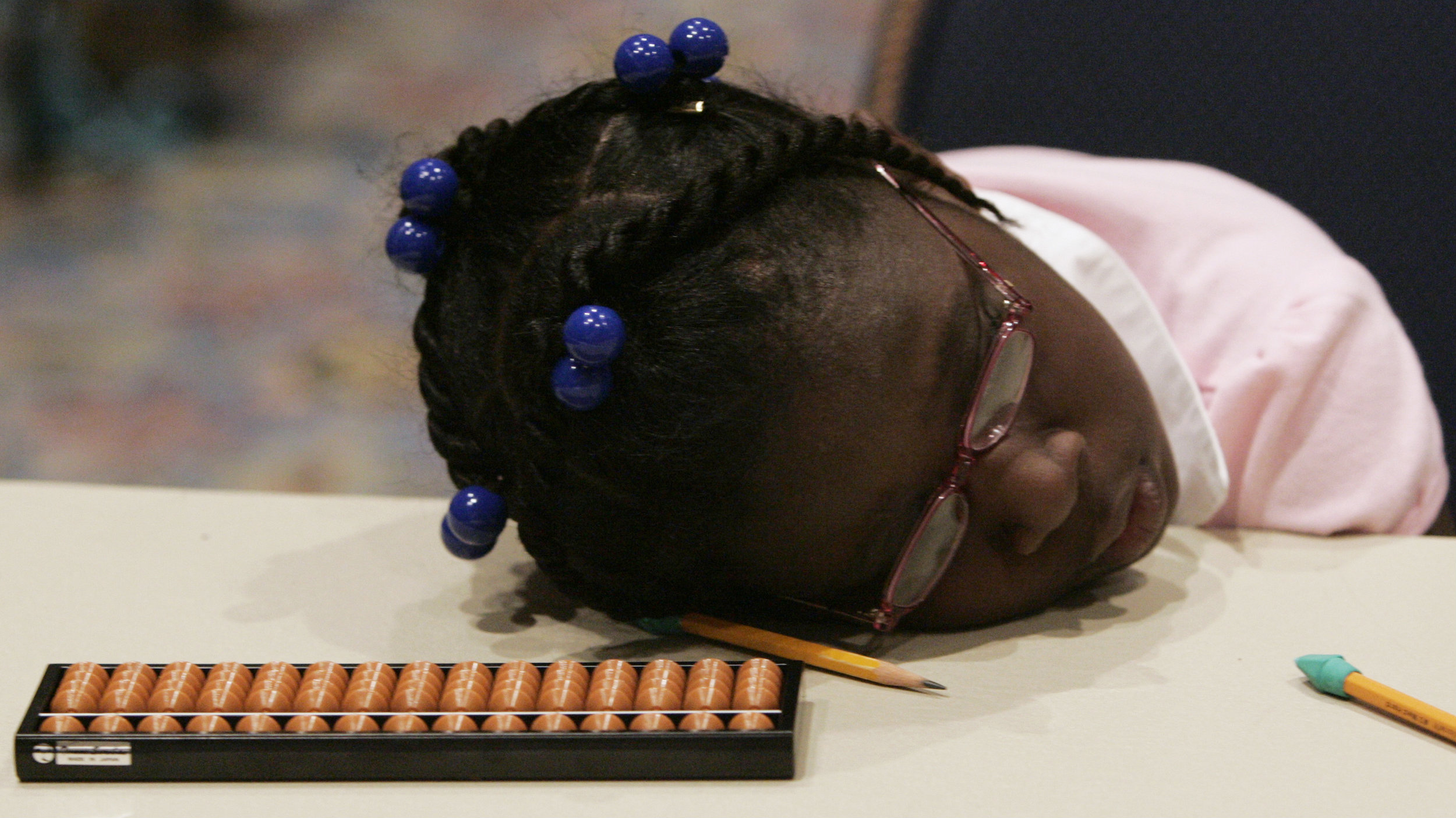 An elementary schoolgirl rests next to a traditional Japanese calculating tool called the soroban (abacus) during the 26th American school soroban contest in Tokyo May 22, 2008. Over 100 children from American schools in U.S. military bases in Japan participated in the competition. REUTERS/Toru Hanai (JAPAN)