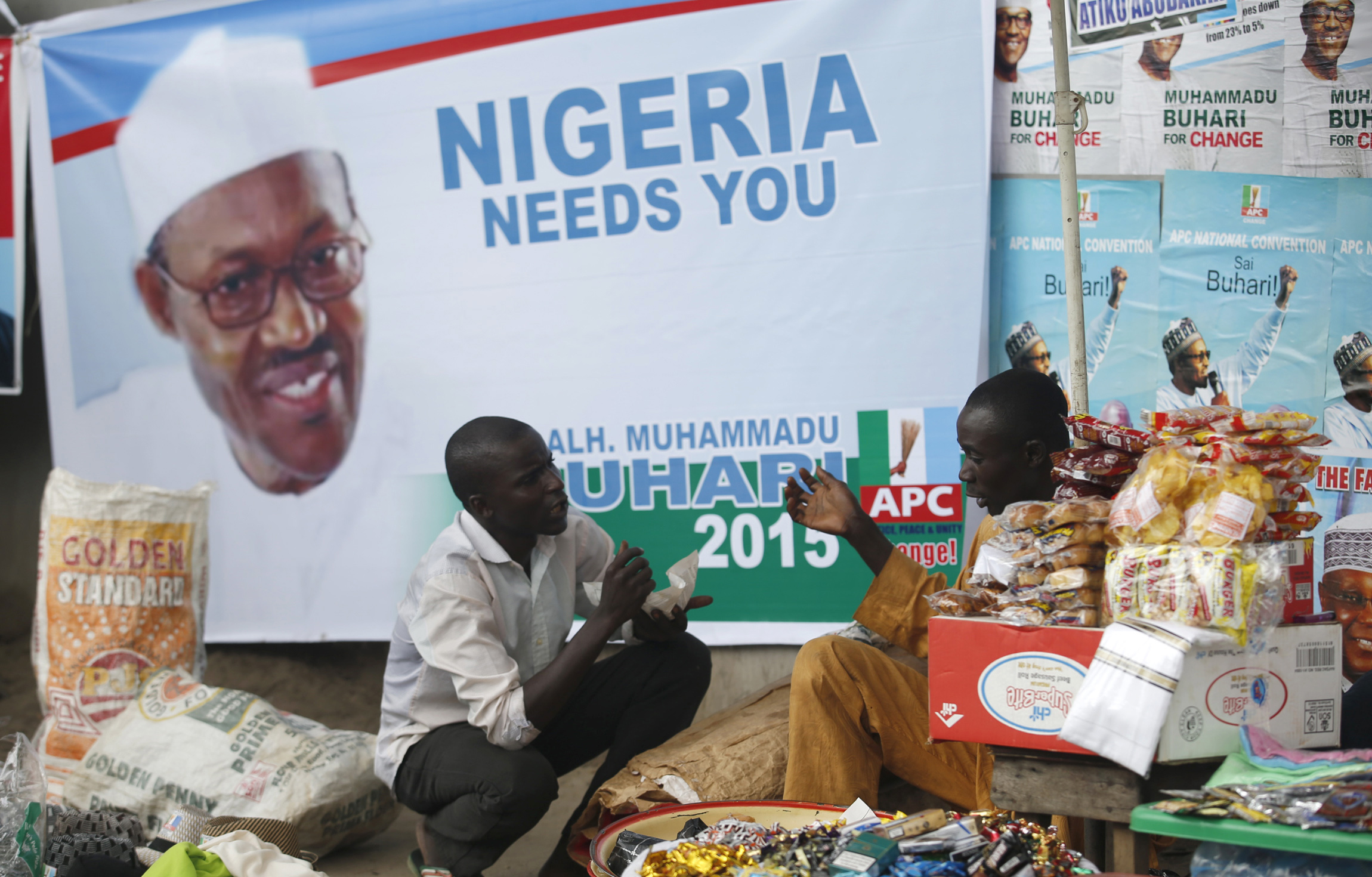 Vendors sell their wares near an election poster of former Nigerian military ruler Muhammadu Buhari before the start of All Progressives Congress (APC) party convention in Lagos December 10, 2014. Nigeria's main opposition coalition began a convention on Wednesday to select a candidate to take on President Goodluck Jonathan in February, in what will be the most closely fought election since the end of military rule in 1999. REUTERS/Akintunde Akinleye  (NIGERIA - Tags: POLITICS ELECTIONS) - RTR4HJ2G