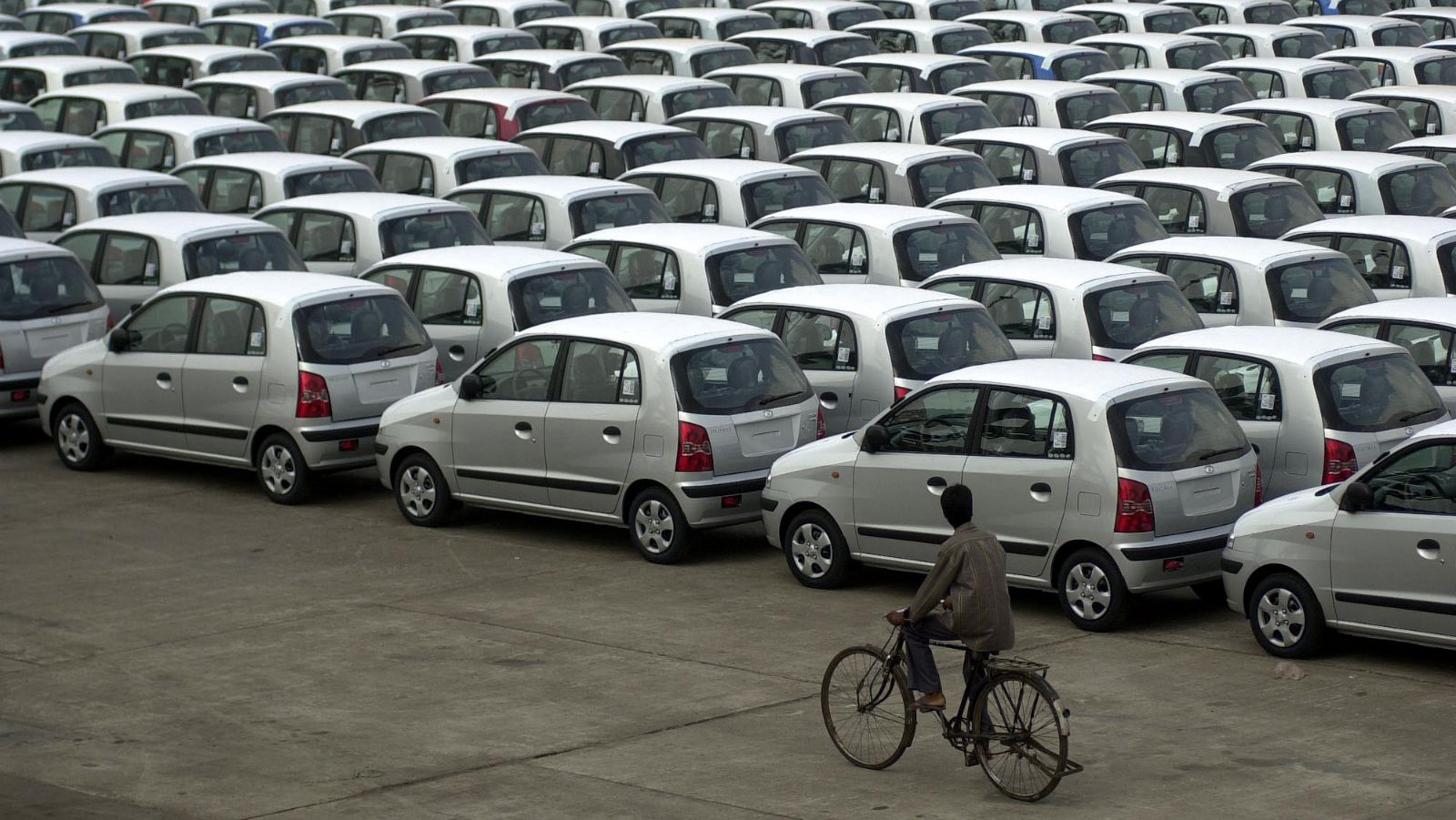 A cyclist goes past Hyundai cars parked at the port in Madras, India, Thursday, March 10, 2005. Hyundai Motor India, which exported nearly 30,000 vehicles in 2004, has targeted shipment of 70,000 cars by 2005. Hyundai India exported cars to Latin America, North Africa, South East Asia, North America and Europe.